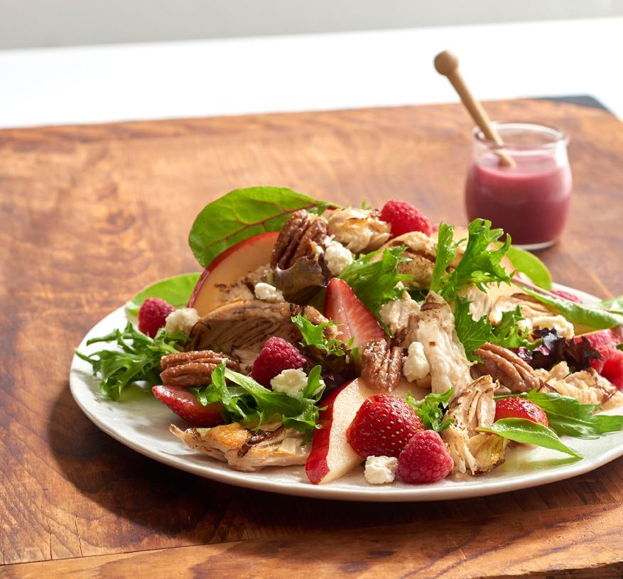 Pear & Berry Salad - Fresh Greens with Charbroiled Chicken, Strawberries, Pears, and Glazed Pecans. We toss it all together with Raspberry Vinaigrette, and top it with Feta Cheese.