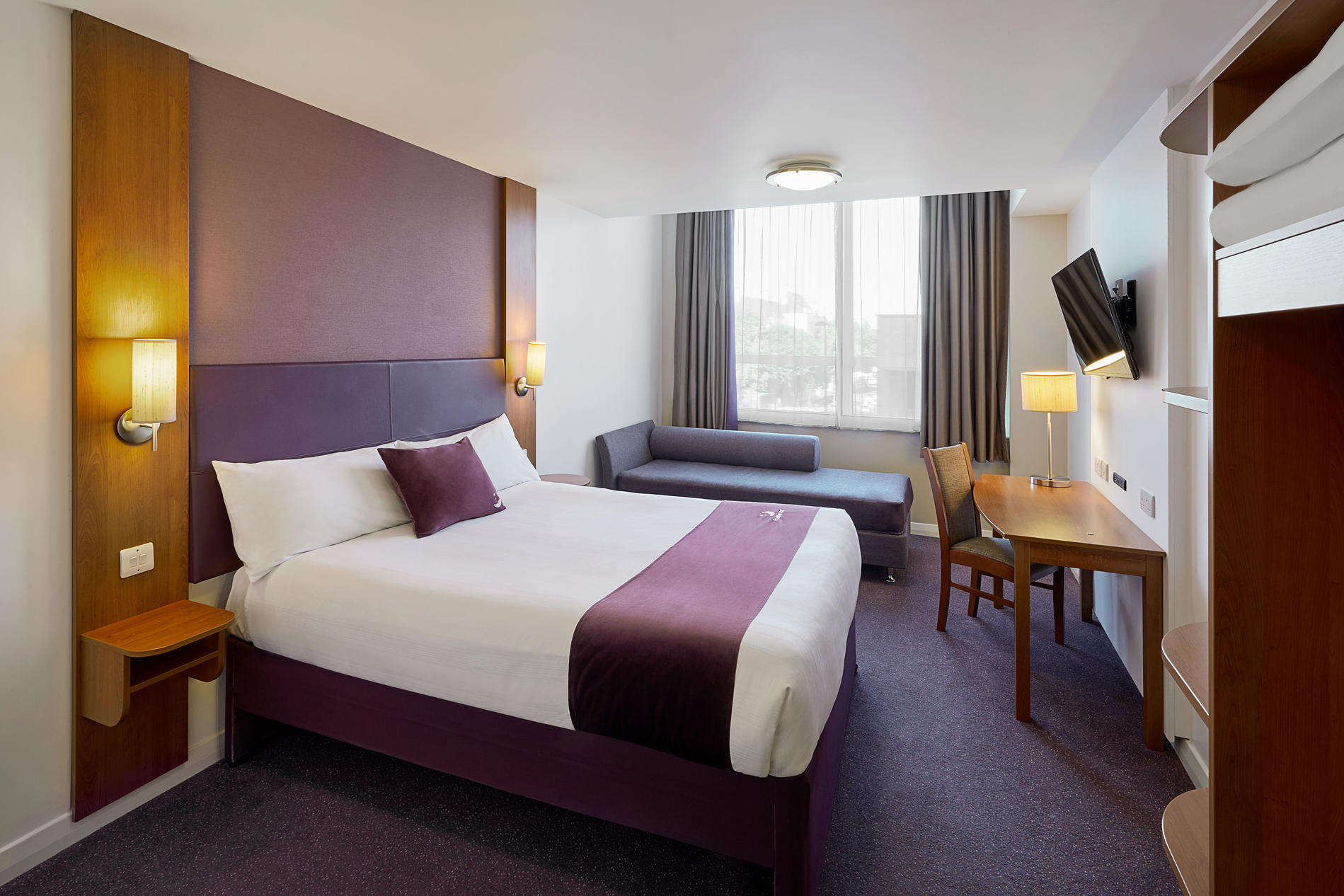 Premier Inn bedroom with double bed, sofa and flat screen TV
