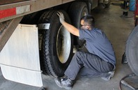 Tire and heavy-duty technicians complete dismount and mount on commercial tire.
