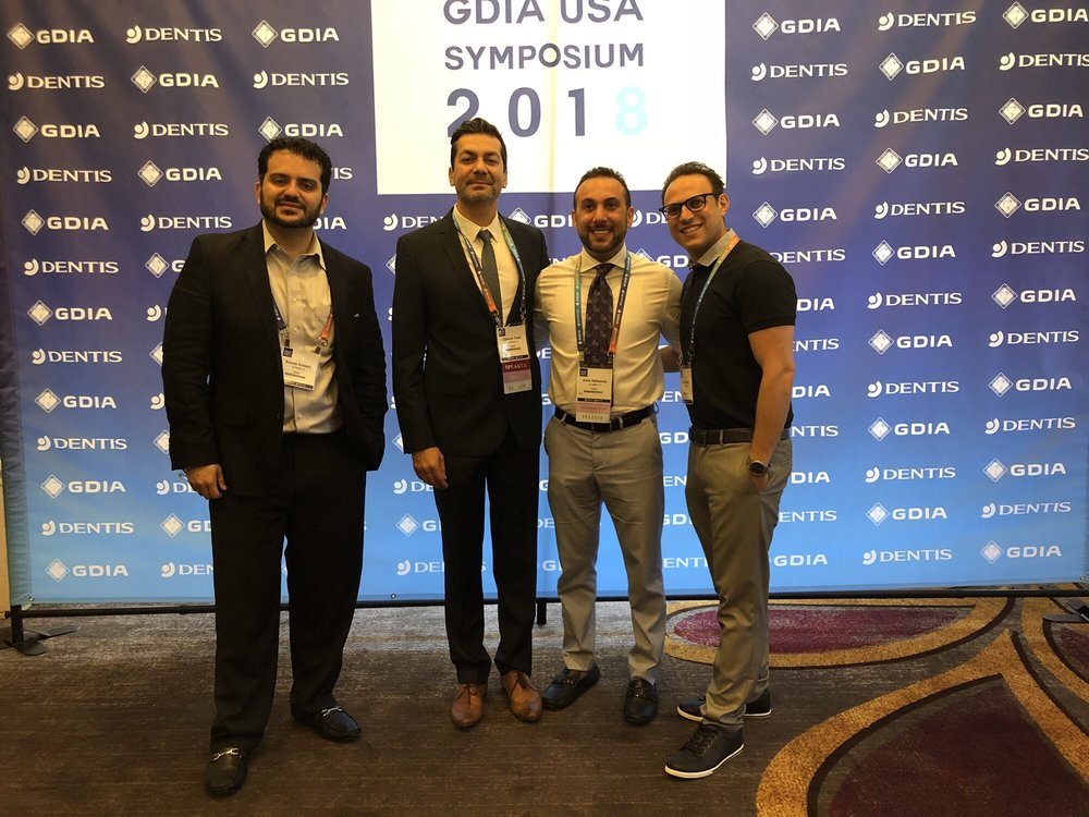 Dr. Torabi, Dr. Hakhamian and Dr. Matian smiling in front of the GDIA banner at an event in Los Angeles, California during 2018.