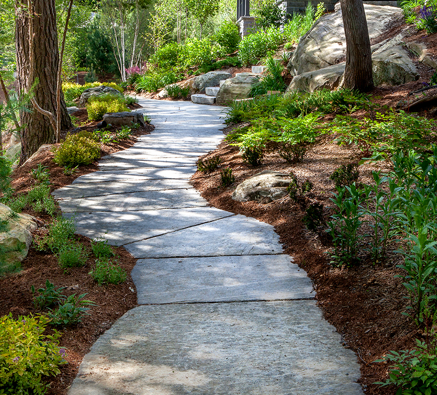HLD Muskoka in Huntsville: Image of a stone walk way winding its way through the forest, built by HLD Muskoka, providers of superior cottage landscaping design and maintenance services in Muskoka.
