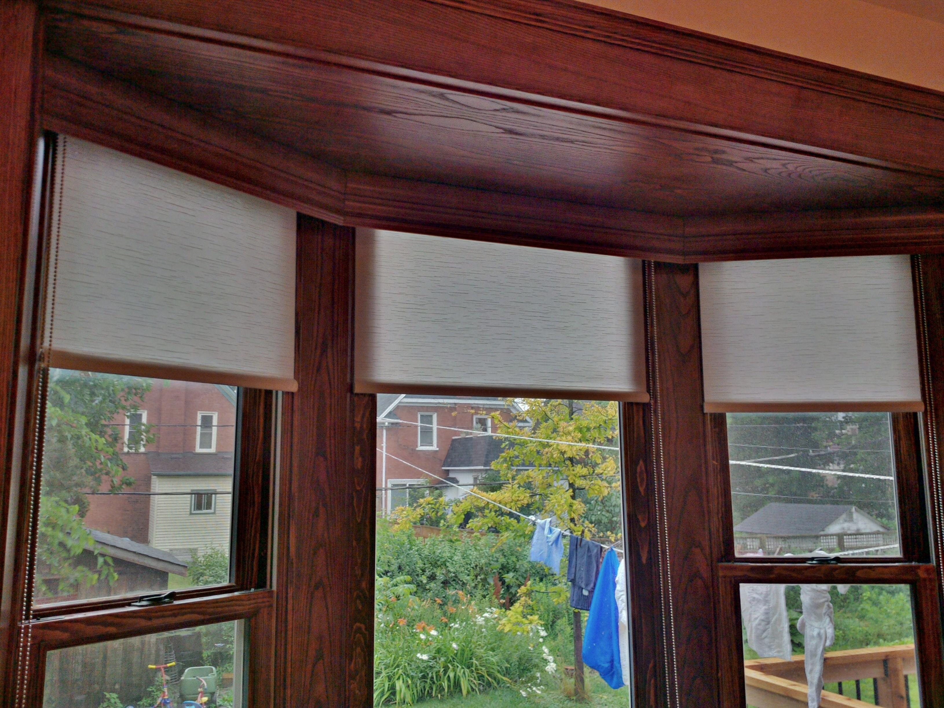 Budget Blinds à Waterloo: This client wanted privacy roller shades that could roll up and hide behind a wood valance that was stained to match their new custom woodwork.