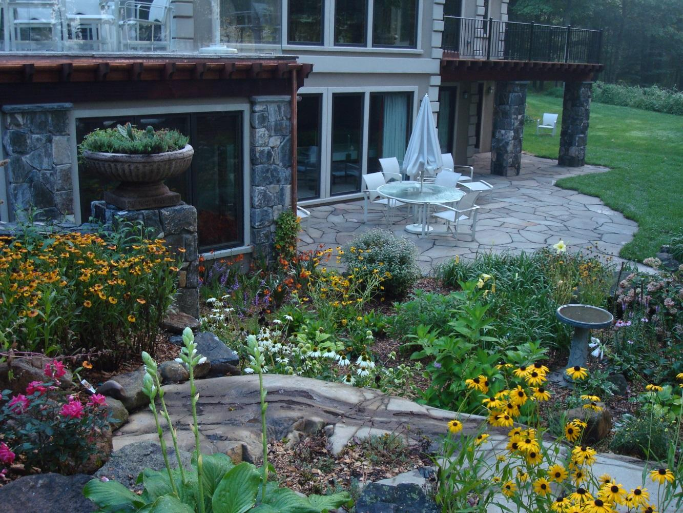 Creating an inviting seating area, planting season to season perennial beds and making natural stone and stone shapes focal point, this back patio received a warm welcome into family's favorite hang-o