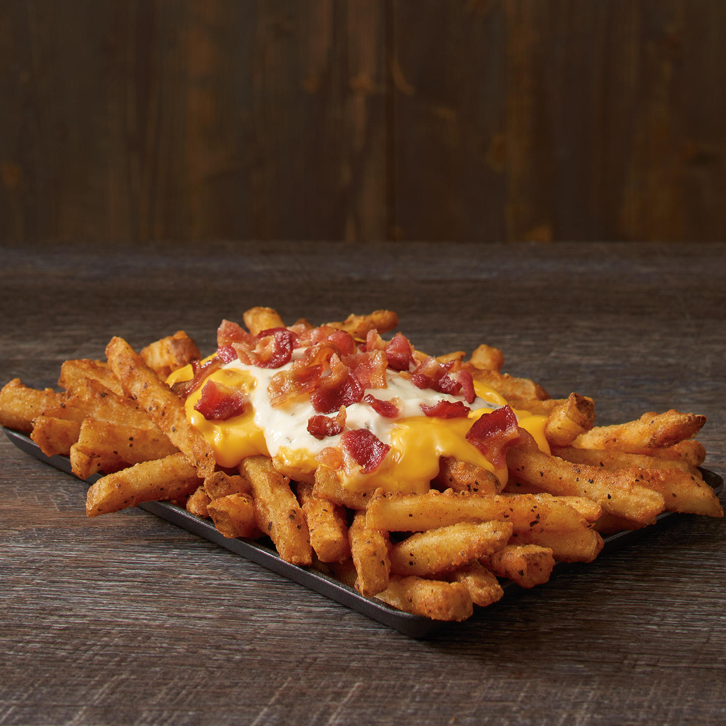 Our Famous Seasoned Fries topped with cheese, ranch and crispy bacon.