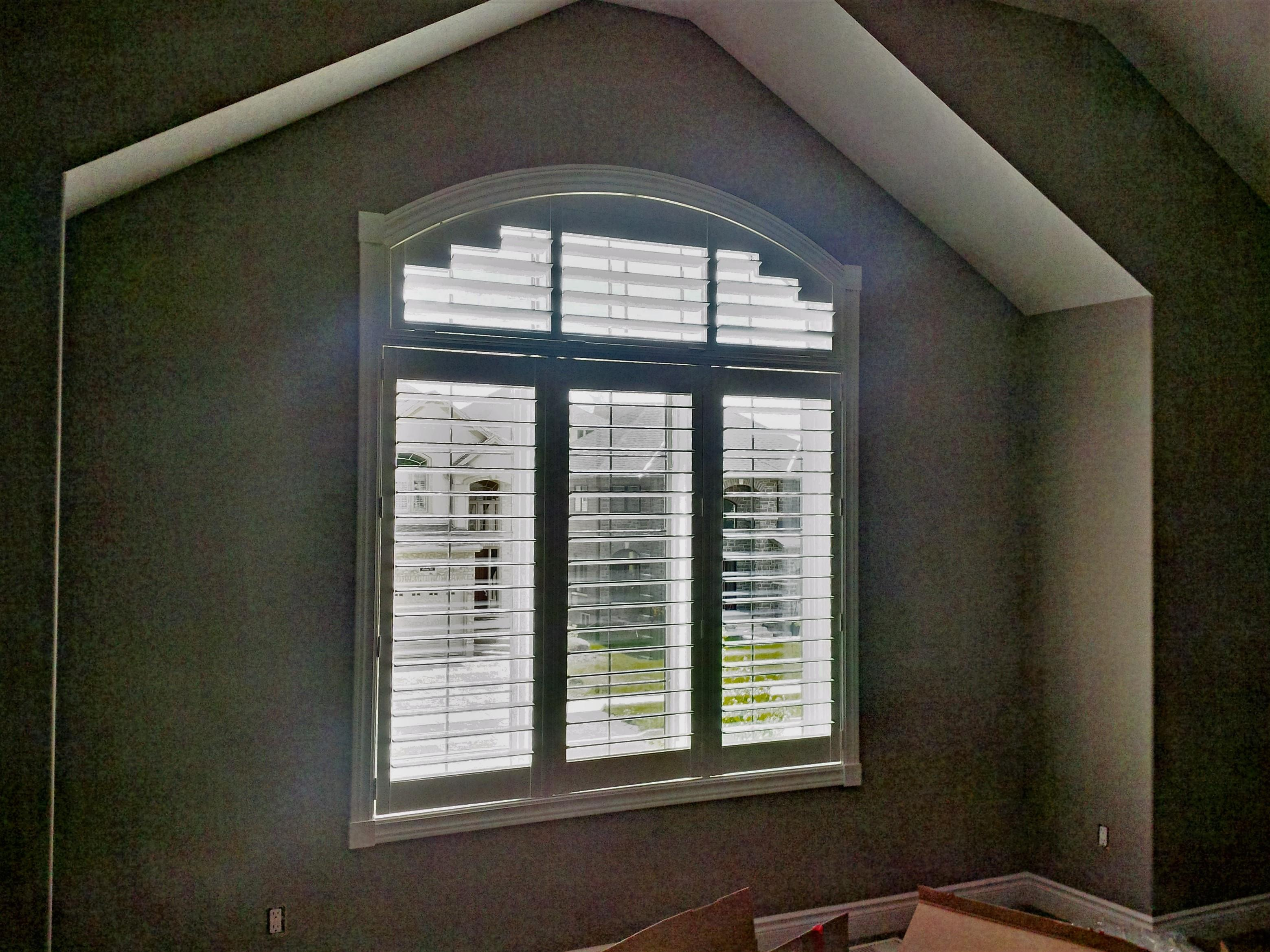 Budget Blinds à Waterloo: This custom designed shutter follows the contour of the arch perfectly. If you require light control in a room with an arched window shutters just might be the most functional option.