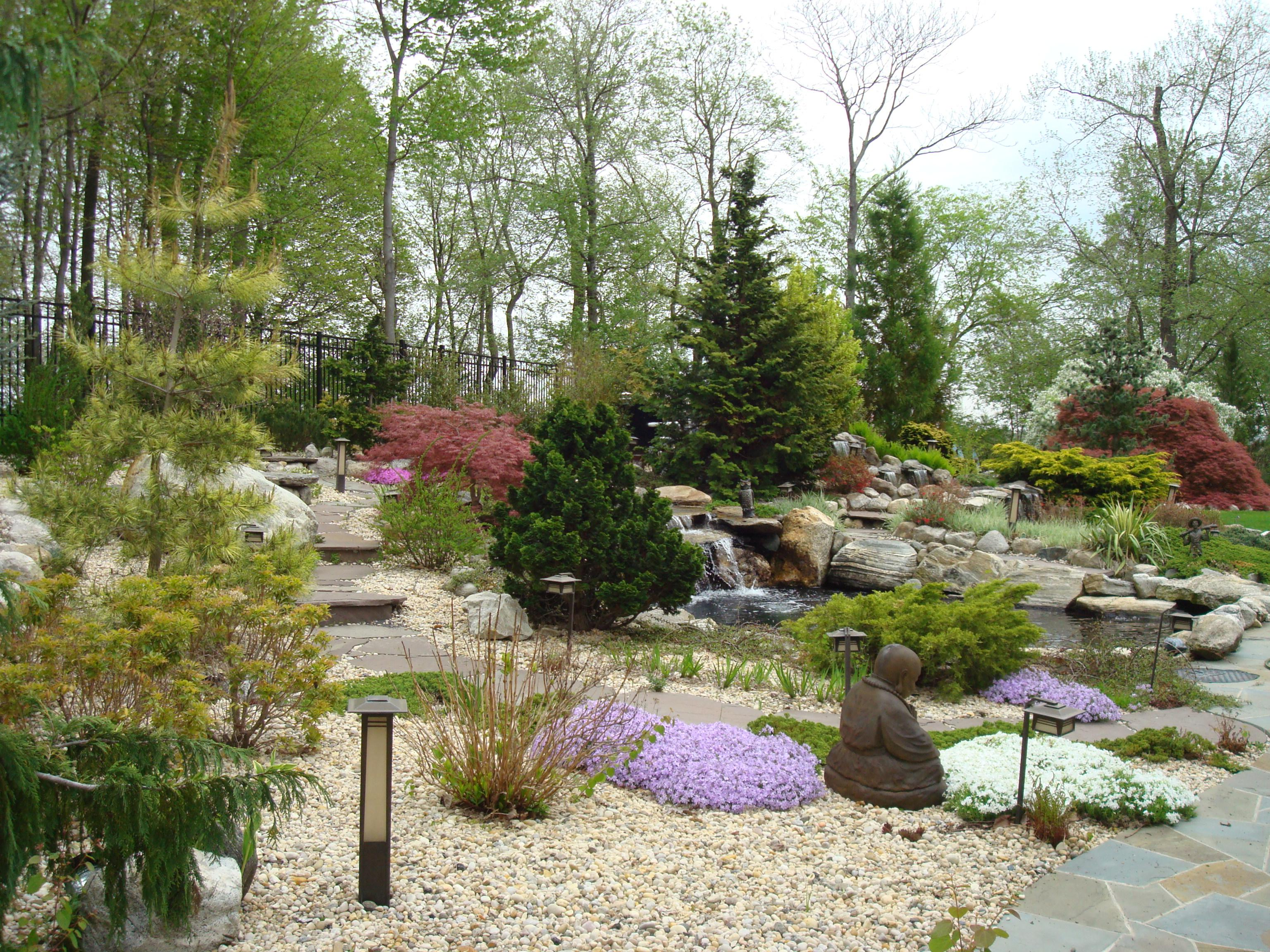 In this specialized landscape design the homeowners love for Asian style gardens was brought together with specimen plants and trees. Specially placed large rocks form unique formations.