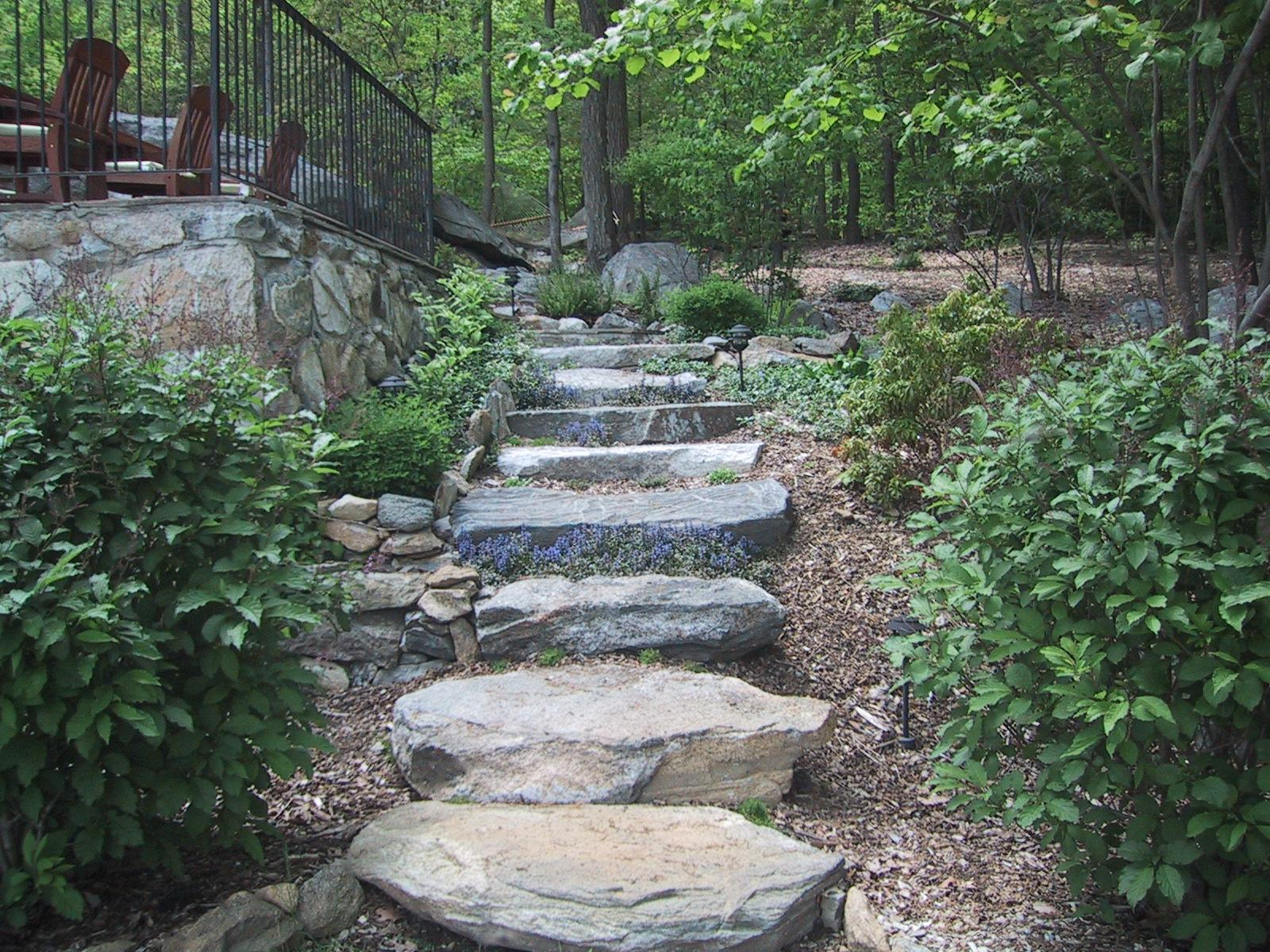 These large stone steps add a natural feel in their woodland setting. They connect the upper outdoor living space to lower lakeside access in a seamless, harmonious way, and are softened by the flower