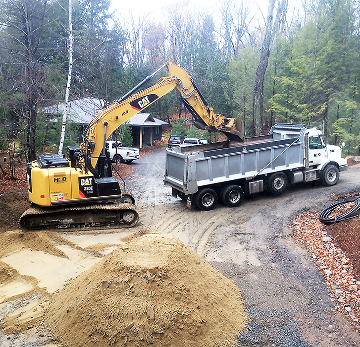 HLD Muskoka in Huntsville: Image of a yellow excavator loading dirt into the back of a dump truck, while being supervised by HLD Muskoka, providers of dependable cottage excavation and site services in Muskoka.