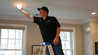 An energy-efficient expert inspecting the LED light bulbs during a home energy assessment.