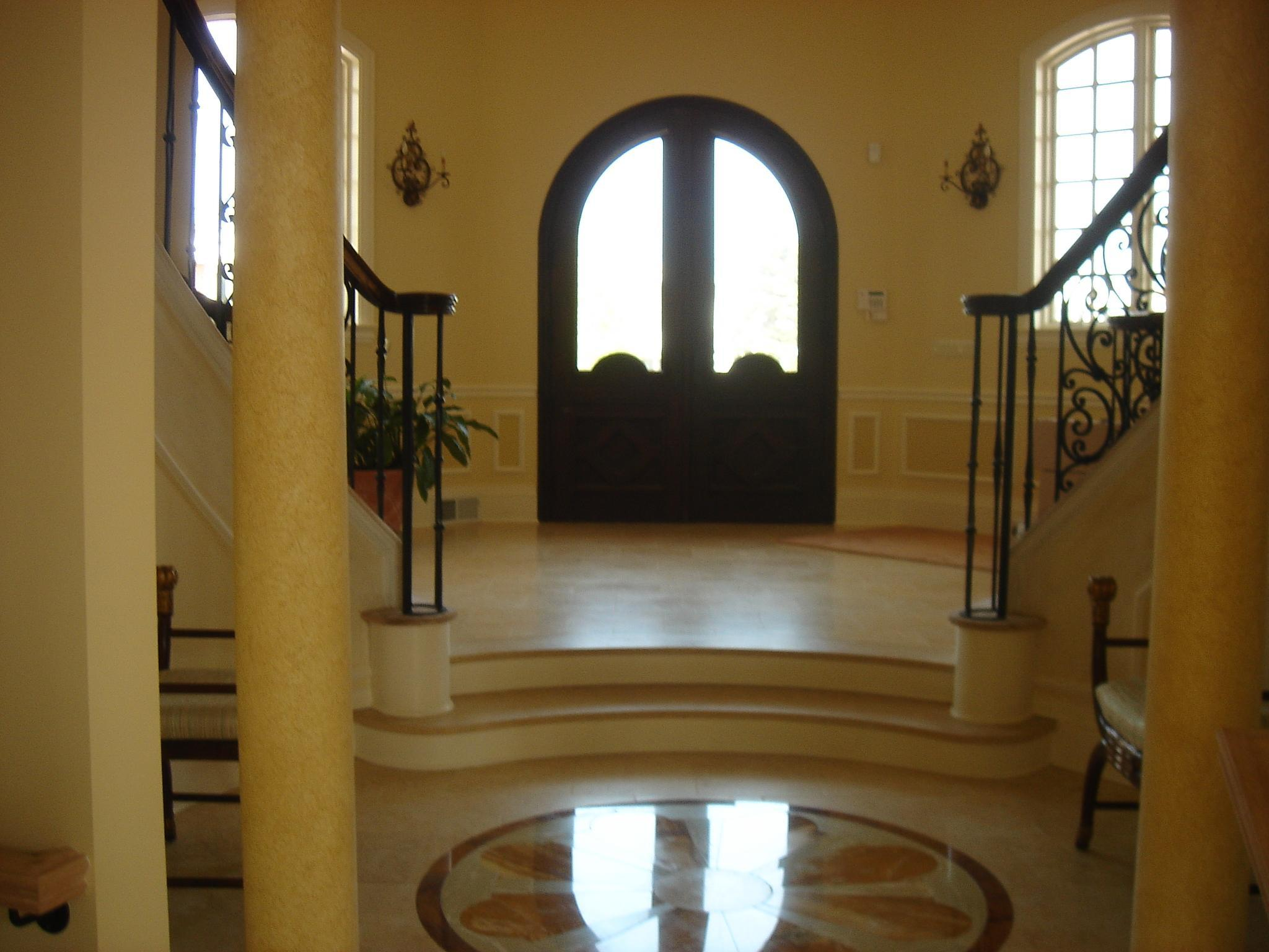 Three story Rotunda Entry with wrought Iron and mahogony wood rail Bridal stair case. Marble and travertine floor.