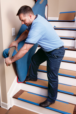 Phoenix movers company putting protective padding on stair railings.