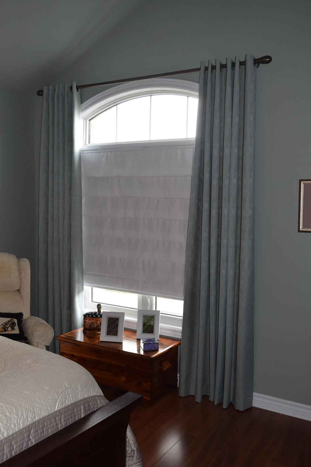 Budget Blinds à Waterloo: During the day the roman shade provides this Stratford customer with privacy and light control. At night the darkening Grommet Drapes can be drawn to prevent light from entering through the arch.