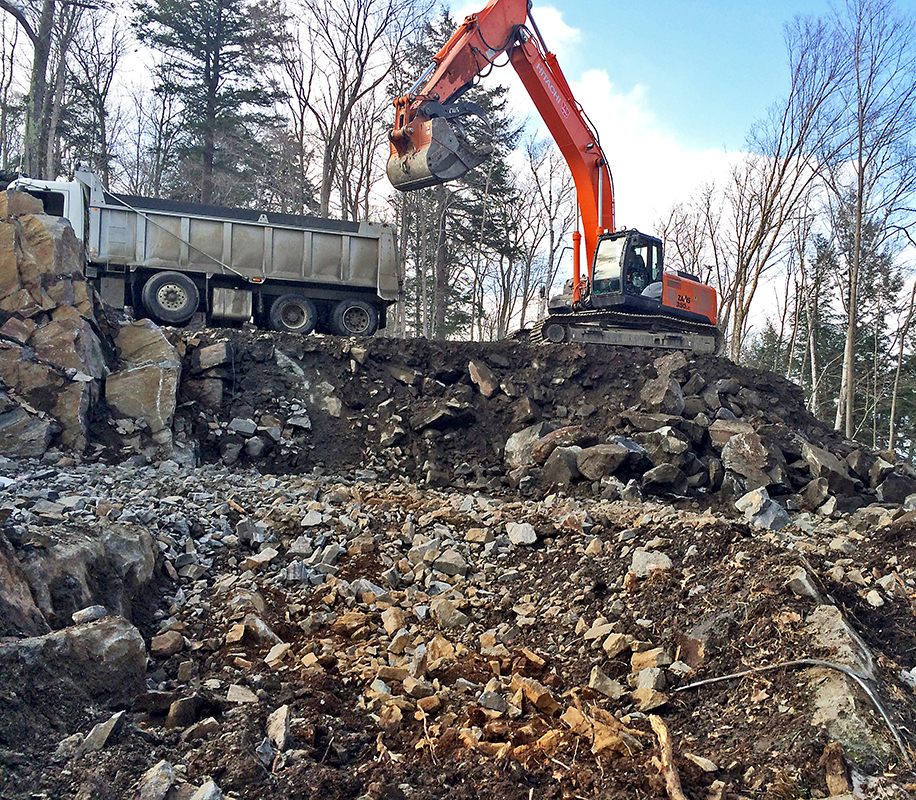 HLD Muskoka in Huntsville: Image of an orange excavator digging the foundation for a cottage, while being supervised by HLD Muskoka, providers of dependable cottage excavation and site services in Muskoka.