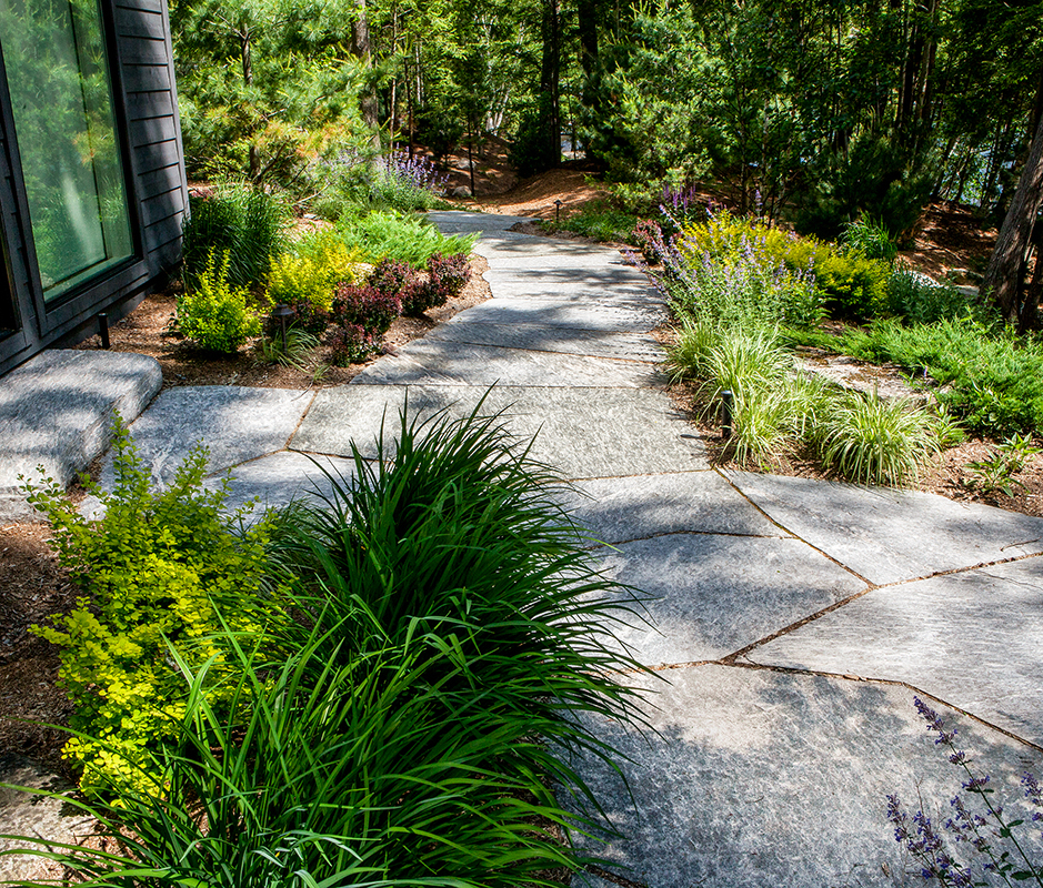 HLD Muskoka in Huntsville: Image of a granite pathway leading from the doorstep--built by HLD Muskoka, providers of superior cottage landscaping design and maintenance services in Muskoka.