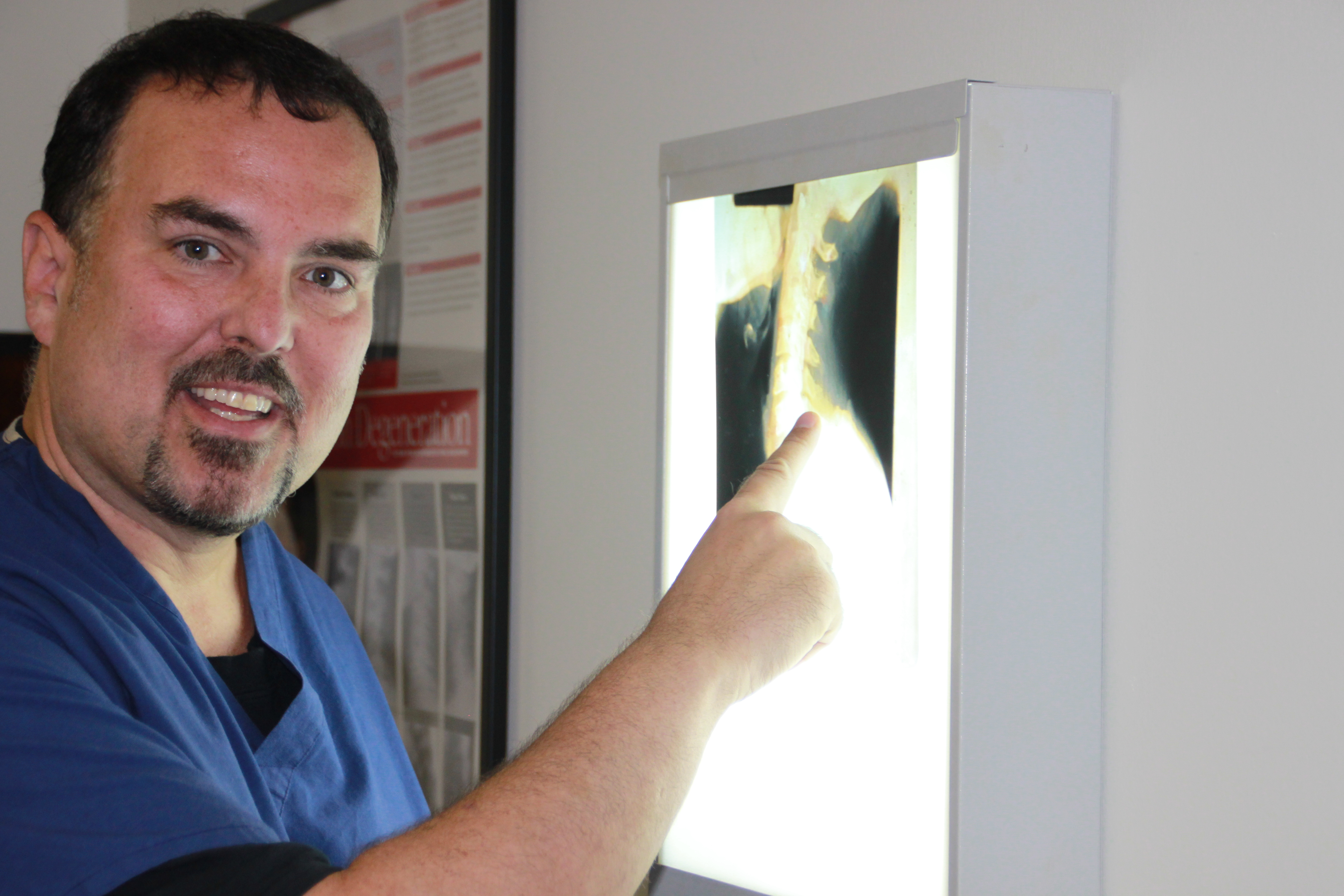 Chiropractor reviewing x rays of cervical degeneration and arthritis