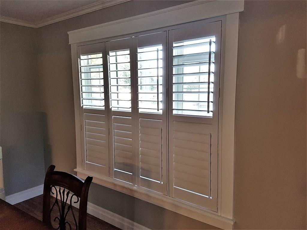 Budget Blinds à Waterloo: This shutter allows flexibility in terms of both privacy and light control  by having a divider rail placed in the centre of the window. Also, by moving the tilt bar off to the side the view is clean and unobstructed.