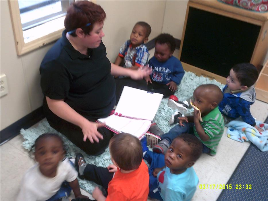 Miss Ashley reads to her class in the Toddler classroom.
