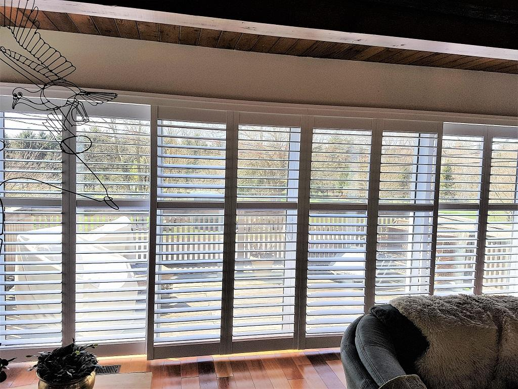 Budget Blinds à Waterloo: This St. Jacob's client had an entire wall of glass that included 2 large sliding patio doors in the centre. The perfect solution was an open-bypass shutter system. The shutter can slide from side to side with the louvres in the completely open position.