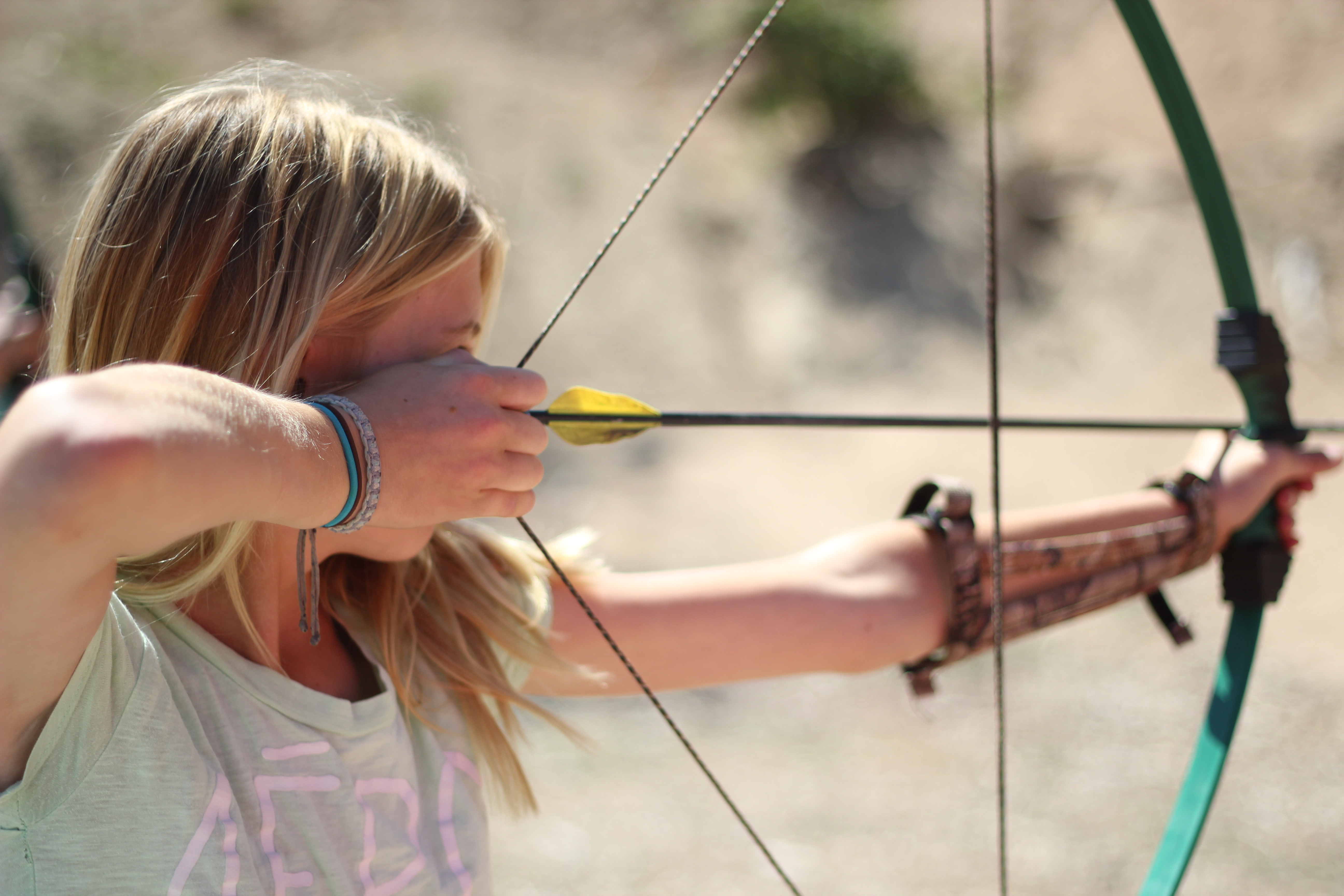 Girl tries archery at Pali Adventures Summer Camp