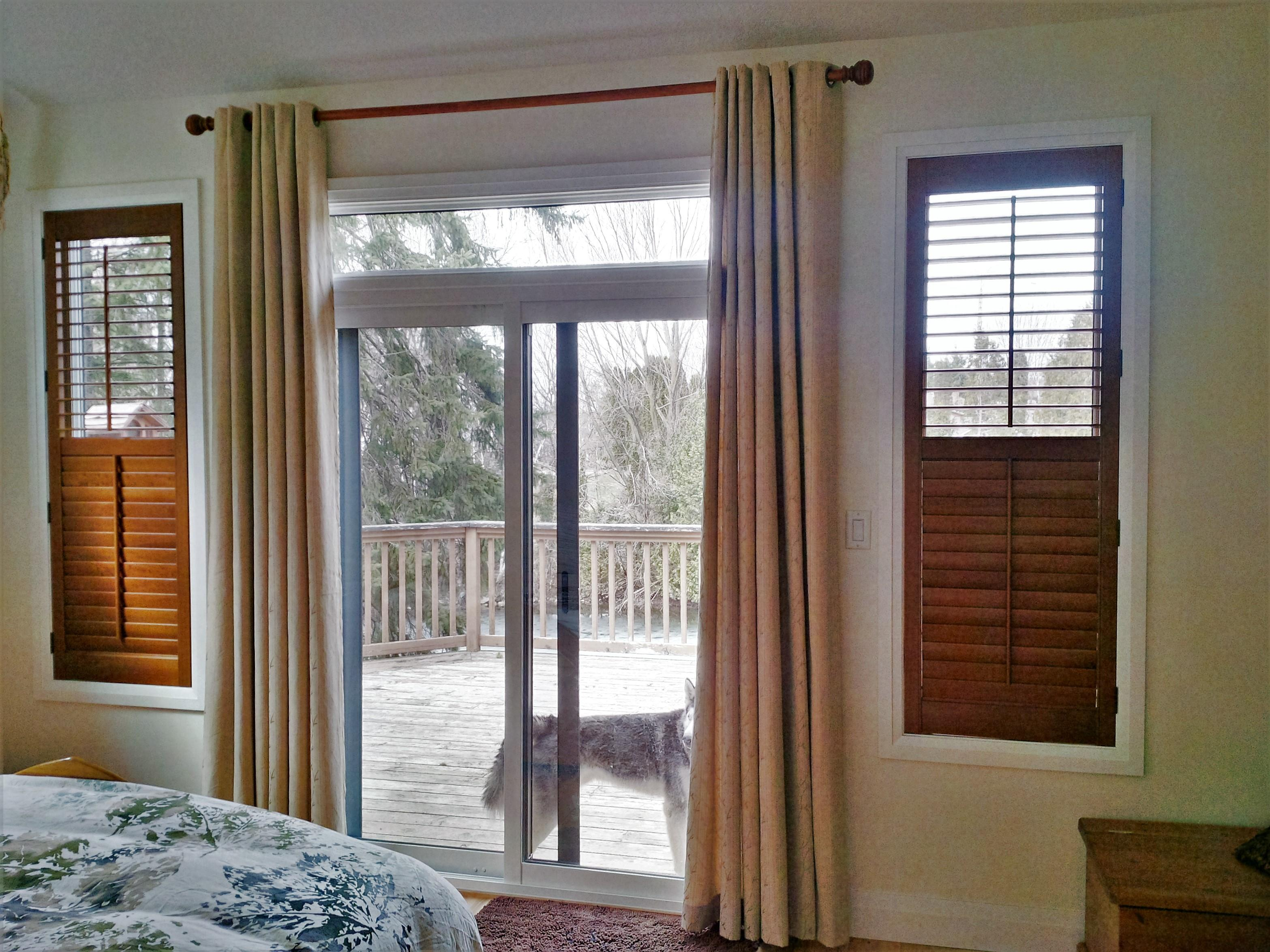 Budget Blinds à Waterloo: The mission for this master bedroom was to bring the outside in. We used solid wood shutters stained to match the wood drapery rod up above. The drapery also added some needed warmth and softness to the space.
