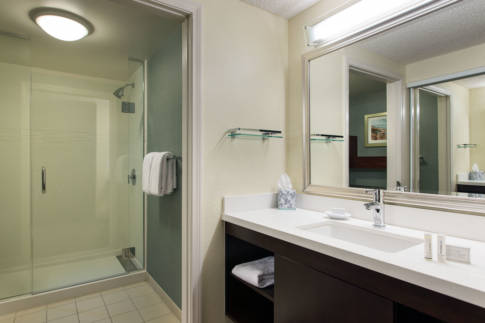 Suite Bathroom - Get ready in style. The vanity area of our refreshed suite bathrooms are brightly lit by mirror lighting and feature thoughtful storage such as shelving and abundant drawer space.