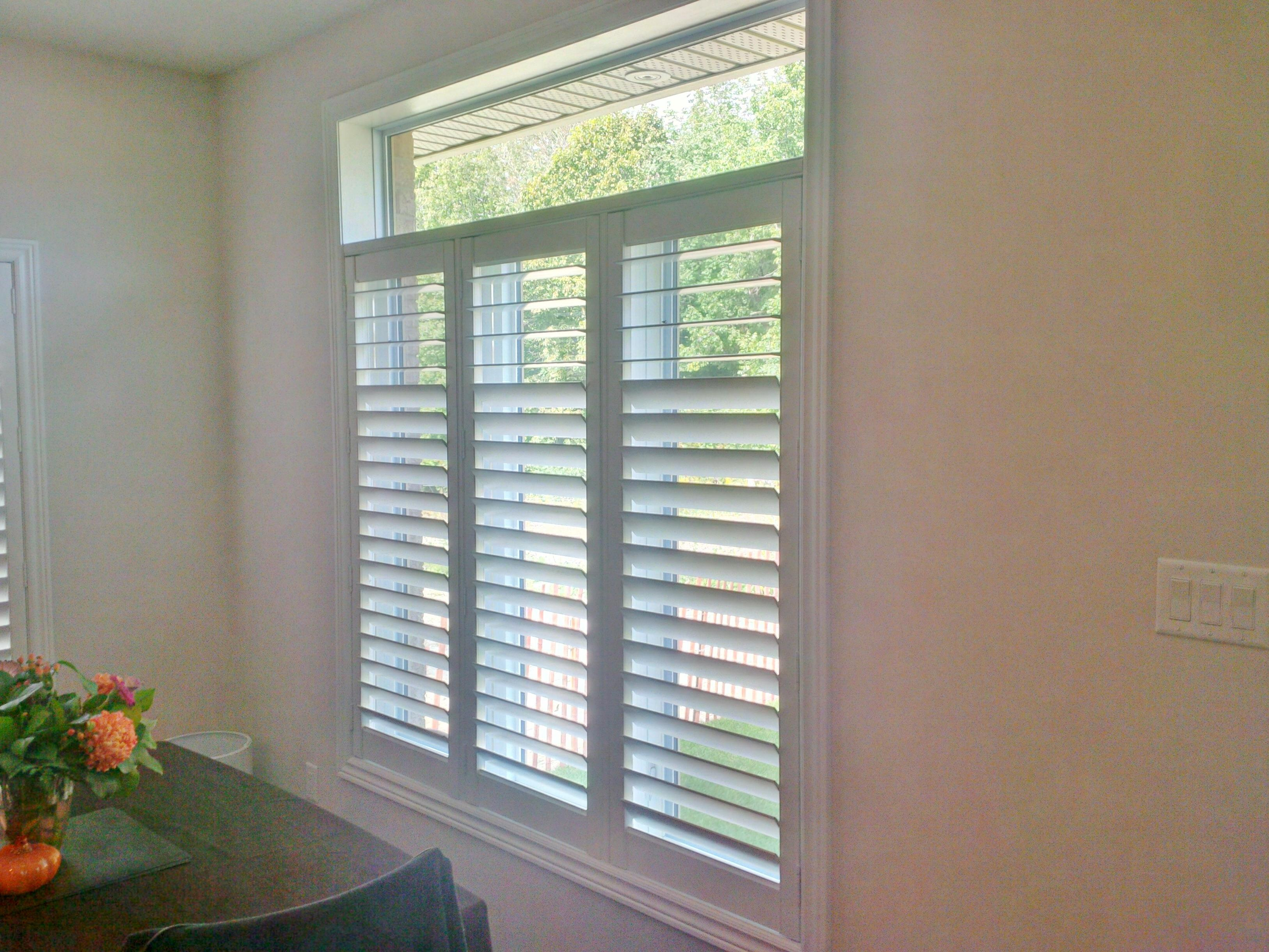 Budget Blinds à Waterloo: It is possible to install shutters with the transom left completely uncovered as we did for this Waterloo customer. They now have privacy and some light control provided by the shutter in the lower portion of the window. This is complemented by always have some natural, unfiltered light entering the room through the upper transom.