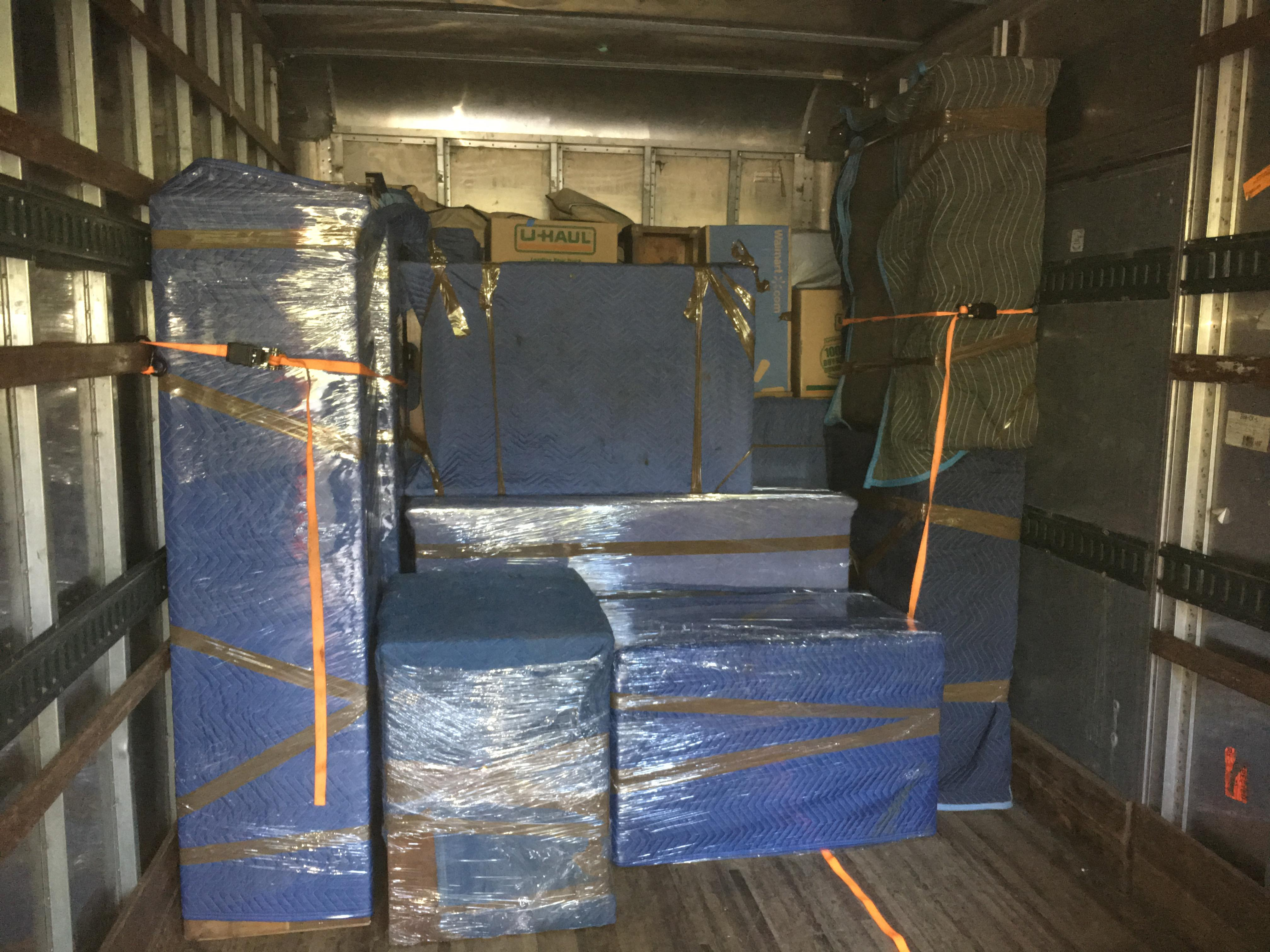 Wrapped furniture stocked in truck during move.
