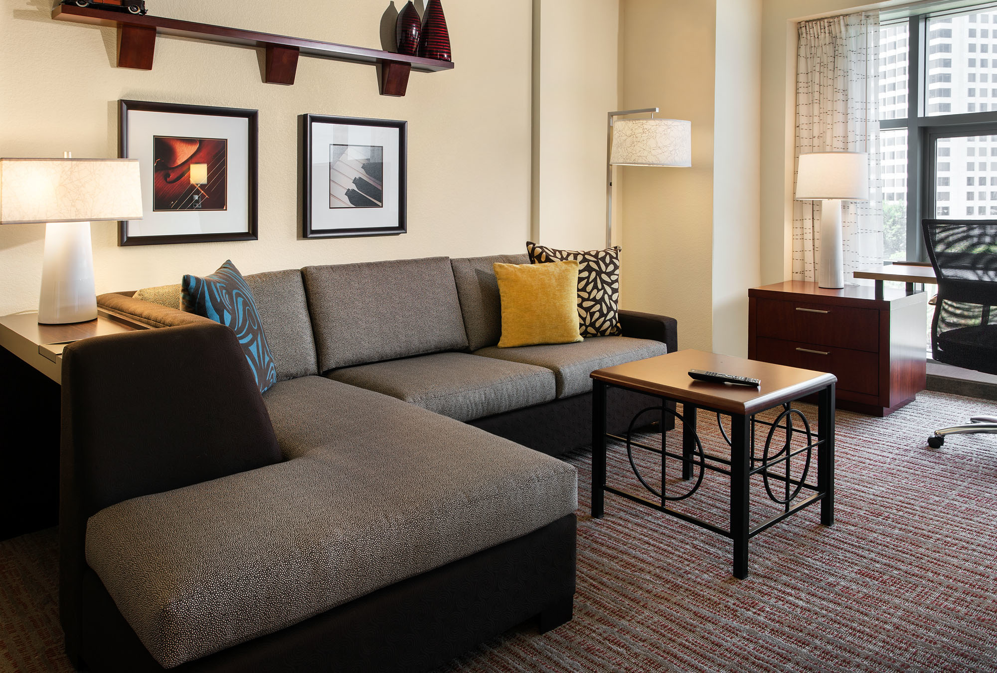Suite Living Area - Our spacious suites are ideal for the business traveler, with a large well-lit desk, ergonomic chair, and easy-to-reach plugs and data port. Each suite also features a fully equipped kitchen and comfortable living area.