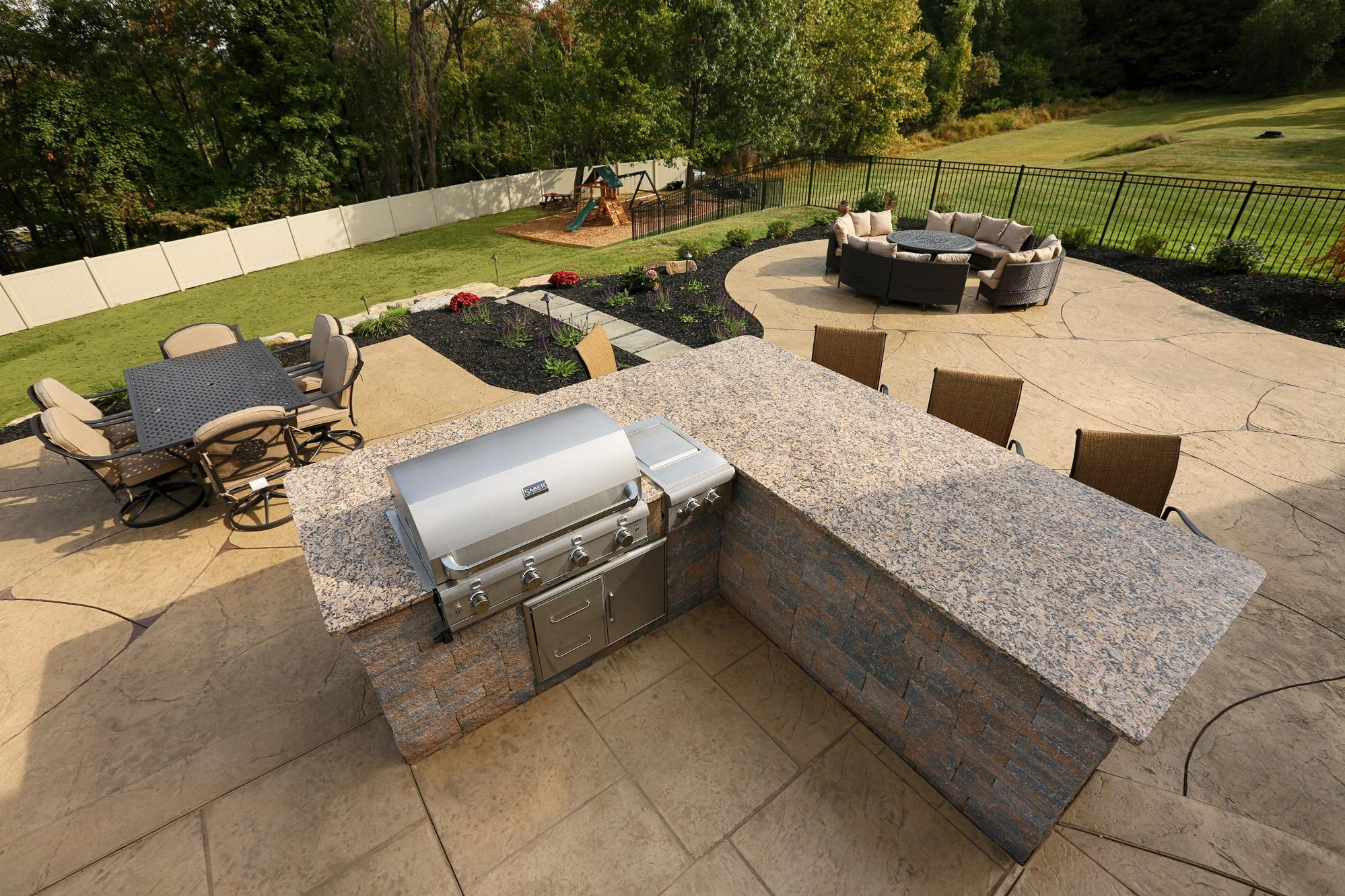 An Outdoor Kitchen On The Top Tier Of Our Two Stamped Concrete Patio Design