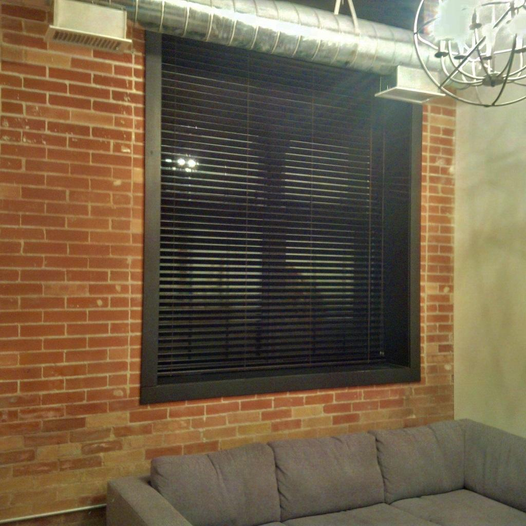 """Budget Blinds à Waterloo: This industrial loft condo had black window casing and the client wanted a solution that would blend right in. We did solid wood 2"""" blinds in a matching black finish."""