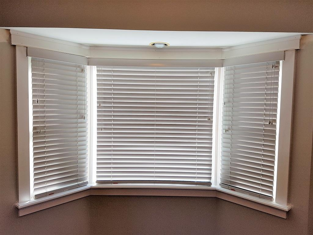"""Budget Blinds à Waterloo: These 2"""" wood blinds were done in a custom colour to coordinate with the homeowner's existing woodwork. The valance was also custom mitered to follow the contour of this Bay window. It doesn't get any more custom than this!"""