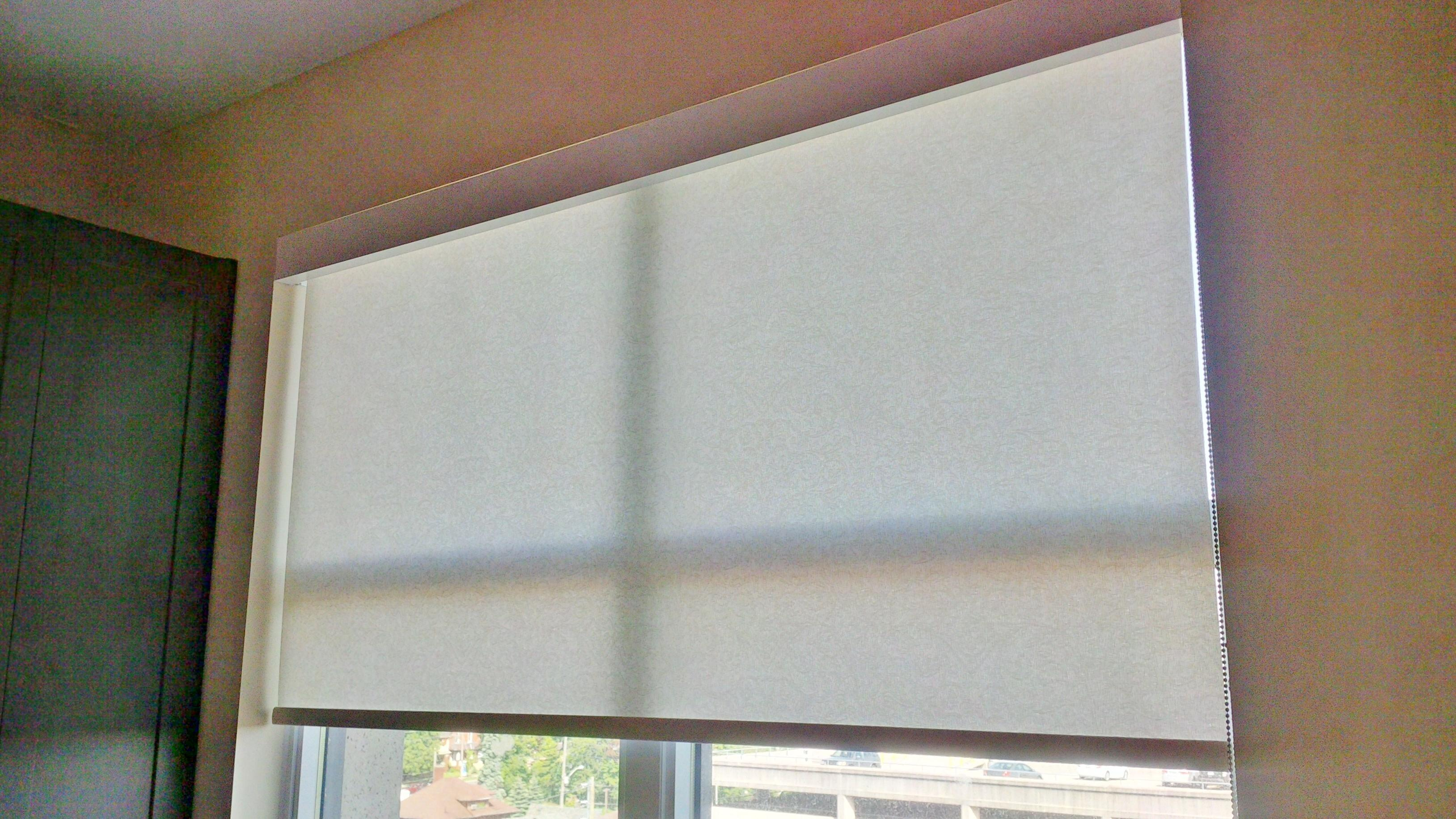 Budget Blinds à Waterloo: Due to the simplicity of operation an the desire to maximize light entering the room, roller shades have become a popular option for covering patio doors.  When not in use it rolls up inside the white aluminum fascia valance .