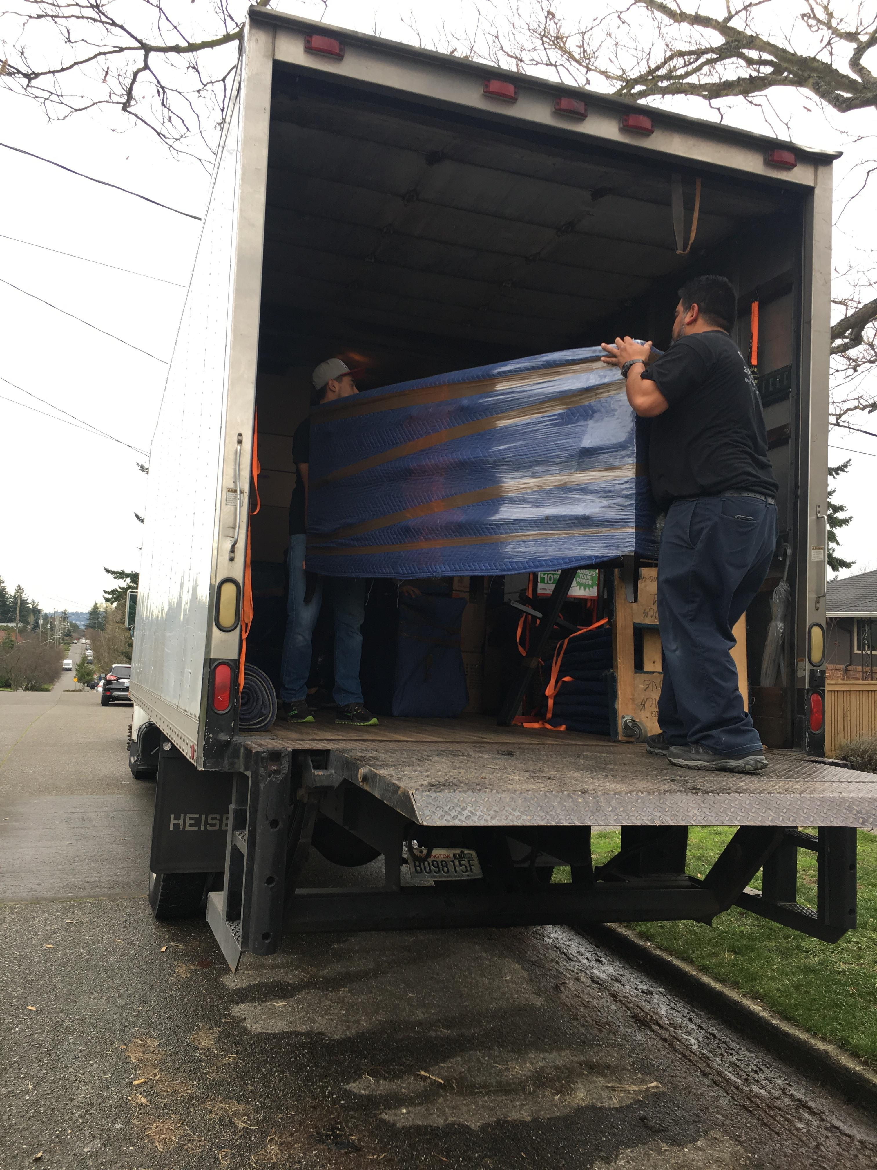 Moving crew carrying wrapped dresser.