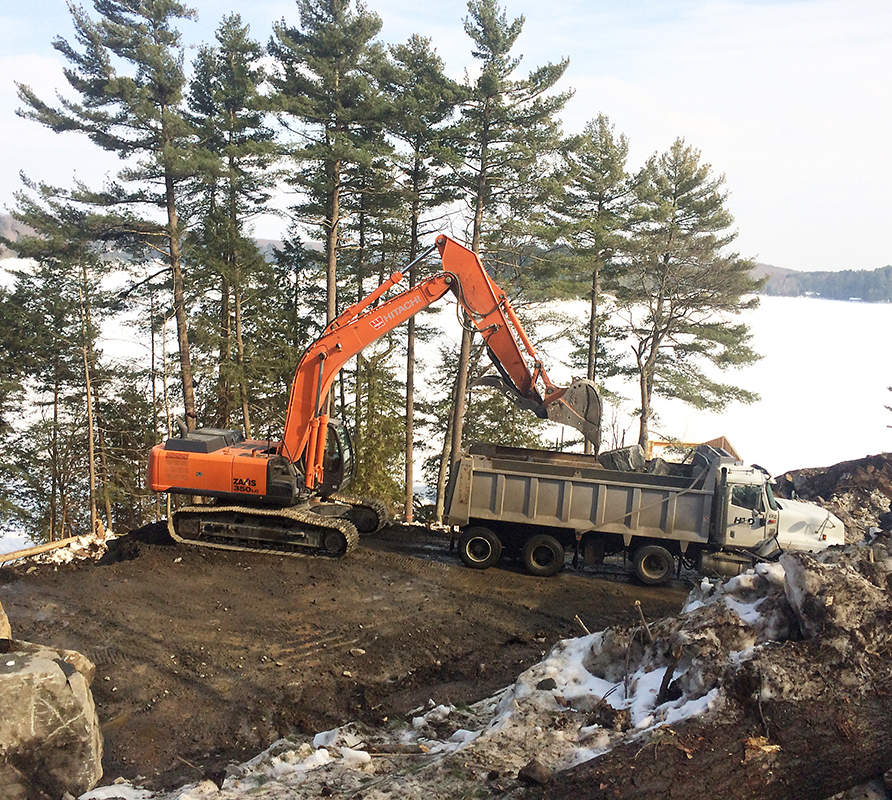 HLD Muskoka in Huntsville: Image of an orange excavator working by the water's edge preparing the ground for a new cottage build, while being supervised by HLD Muskoka, providers of dependable cottage excavation and site services in Muskoka.
