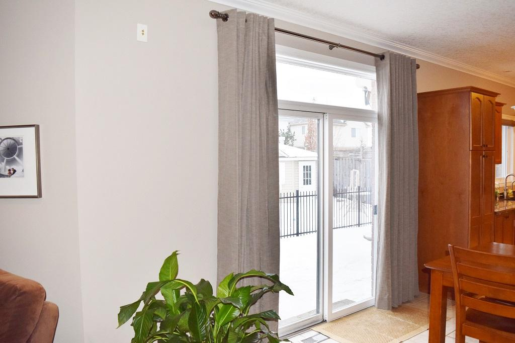 Budget Blinds à Waterloo: Drapery is an excellent option for covering a patio door if you're looking for something that has a custom feel.
