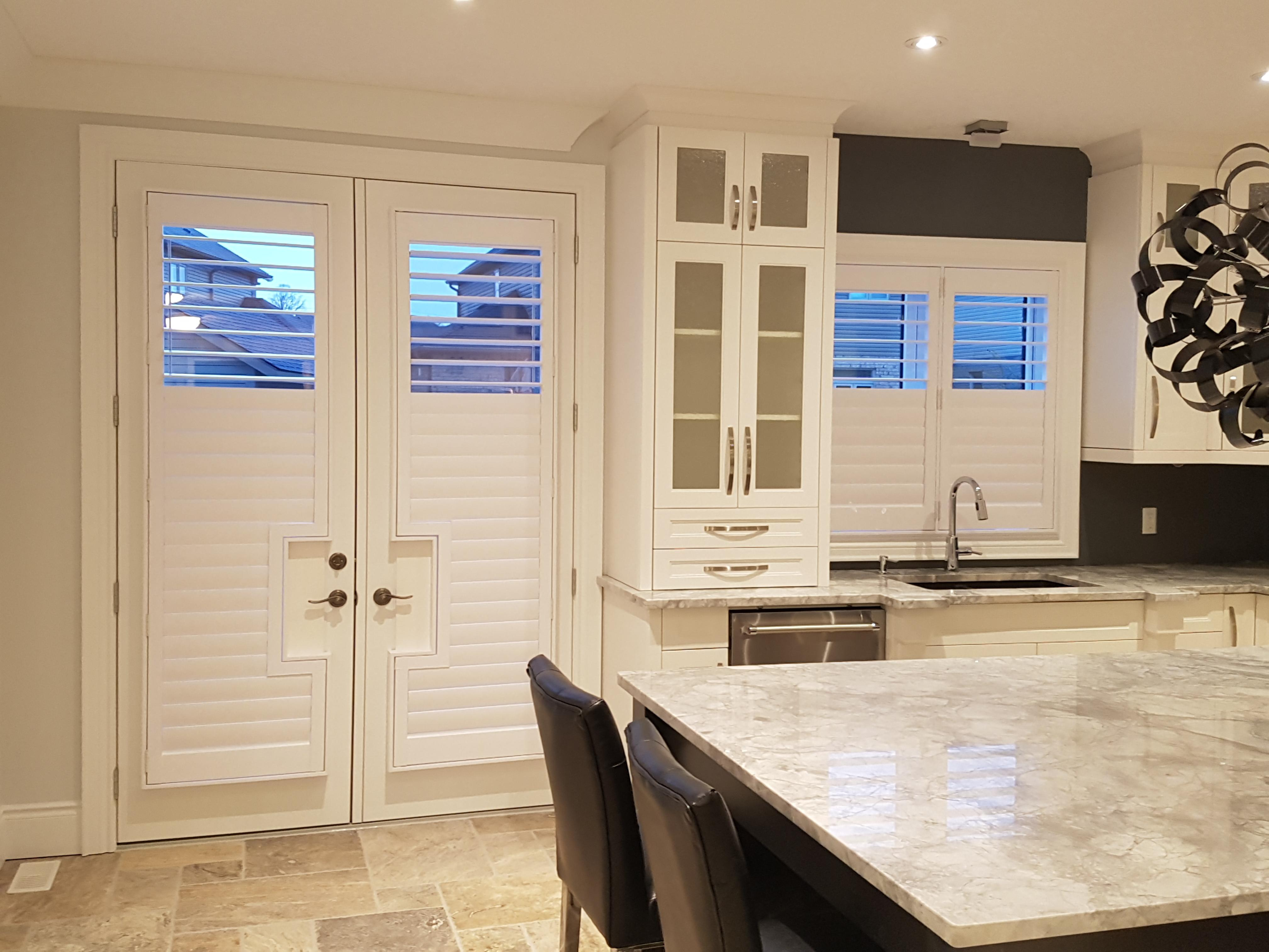 Budget Blinds à Waterloo: These white California Shutters blend into this white kitchen seamlessly. Notice how the shutters were custom manufactured to accommodate the door hardware. Also, the split tilt in the louvres lines up perfectly even though the shutters are different heights. This is the type of detail that our clients have come to appreciate and expect from Budget Blinds of Waterloo.