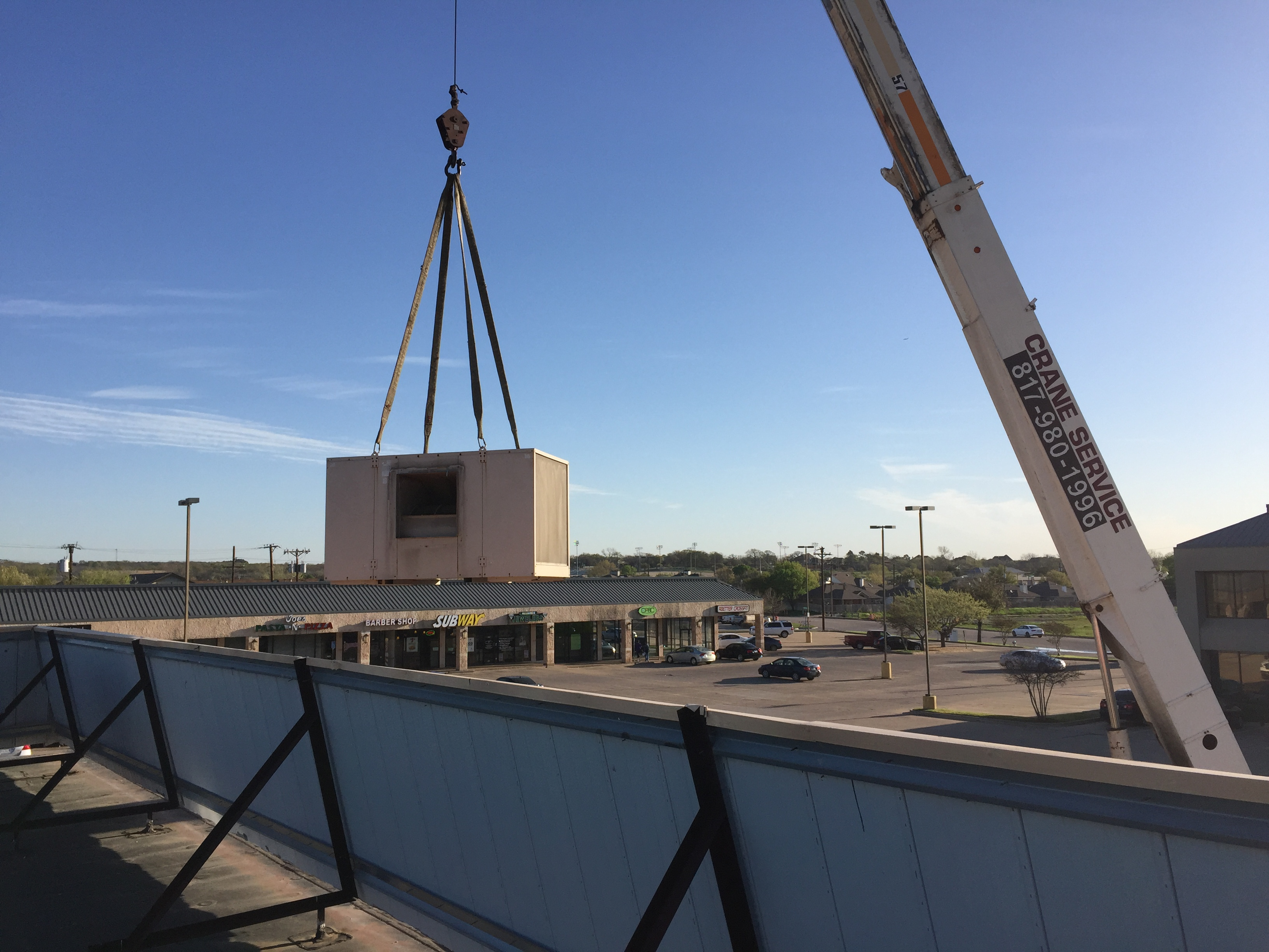 Crane lifting a cooler on the roof