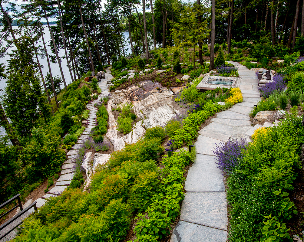 HLD Muskoka in Huntsville: Image of a stone pathway, which winds its way past various gardens, down to a landing by the lake--built by HLD Muskoka, providers of superior cottage landscaping design and maintenance services in Muskoka.
