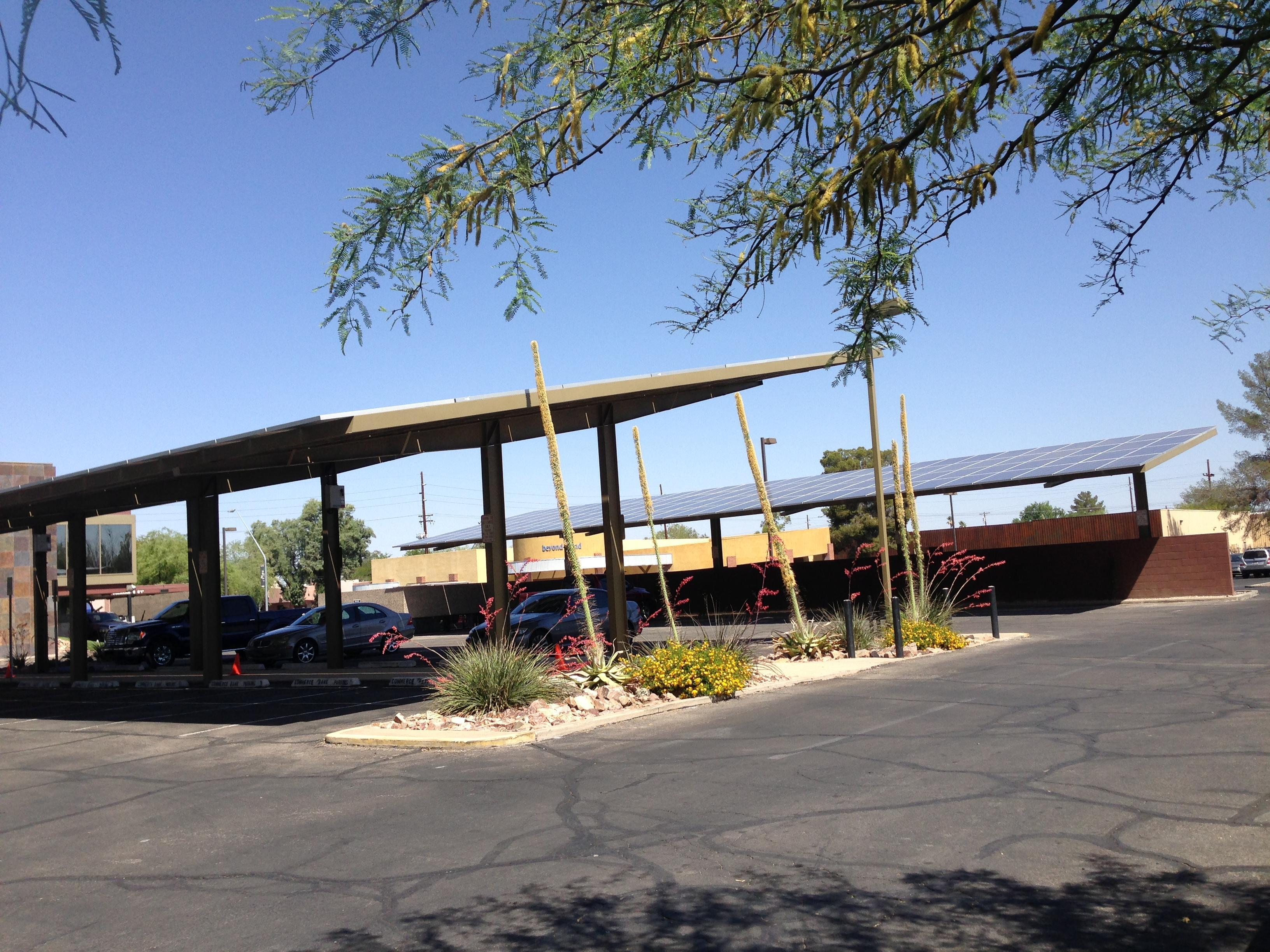 Integrated 100kW solar shade canopy and roof system for Town West Realty - Tucson, AZ.