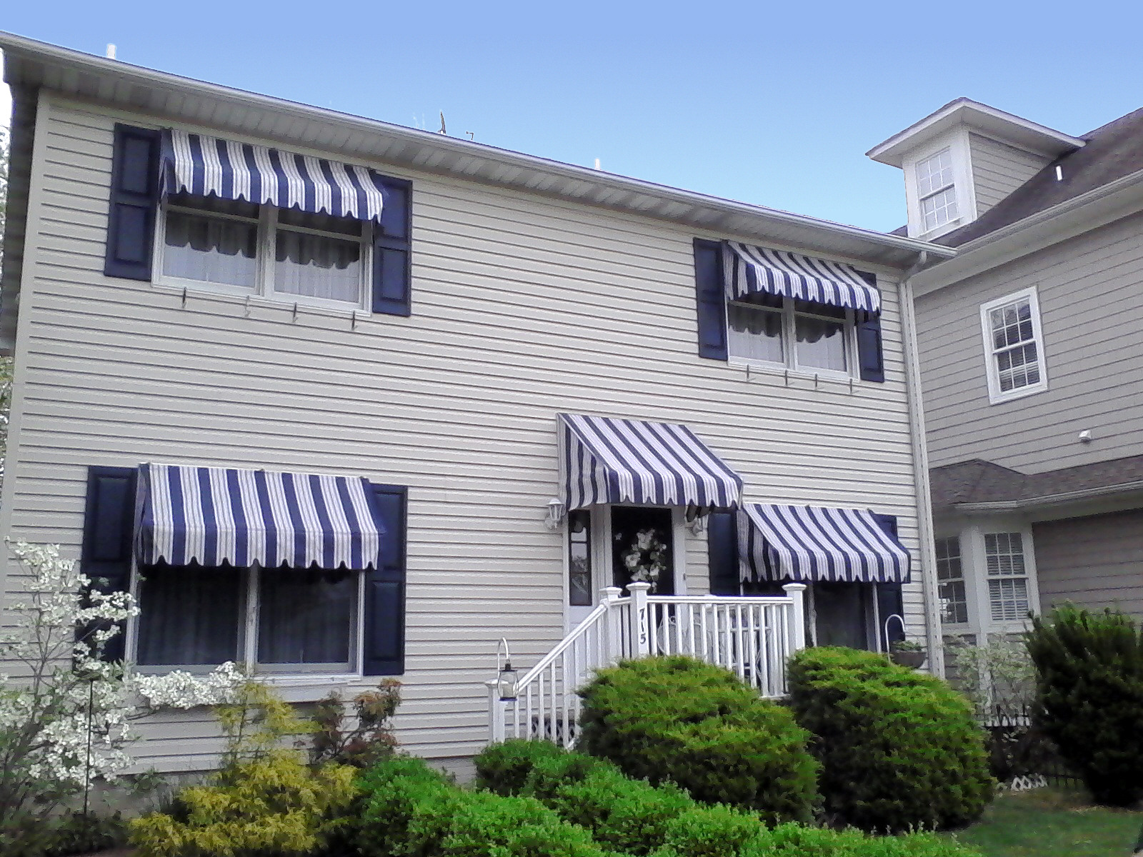 Blue and white striped awnings really set this home off A. Hoffman Awning in Baltimore     410-685-5687