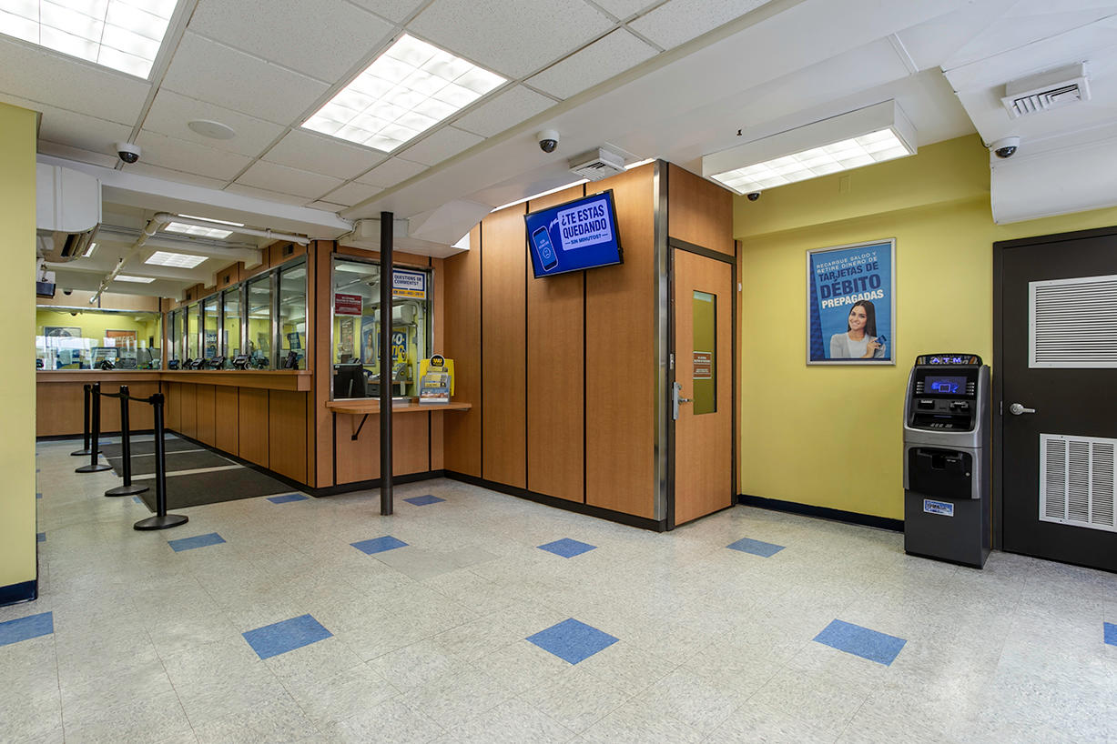 Customer waiting area and teller windows inside PAYOMATIC store located at 590 Eight Ave New York, NY 10018