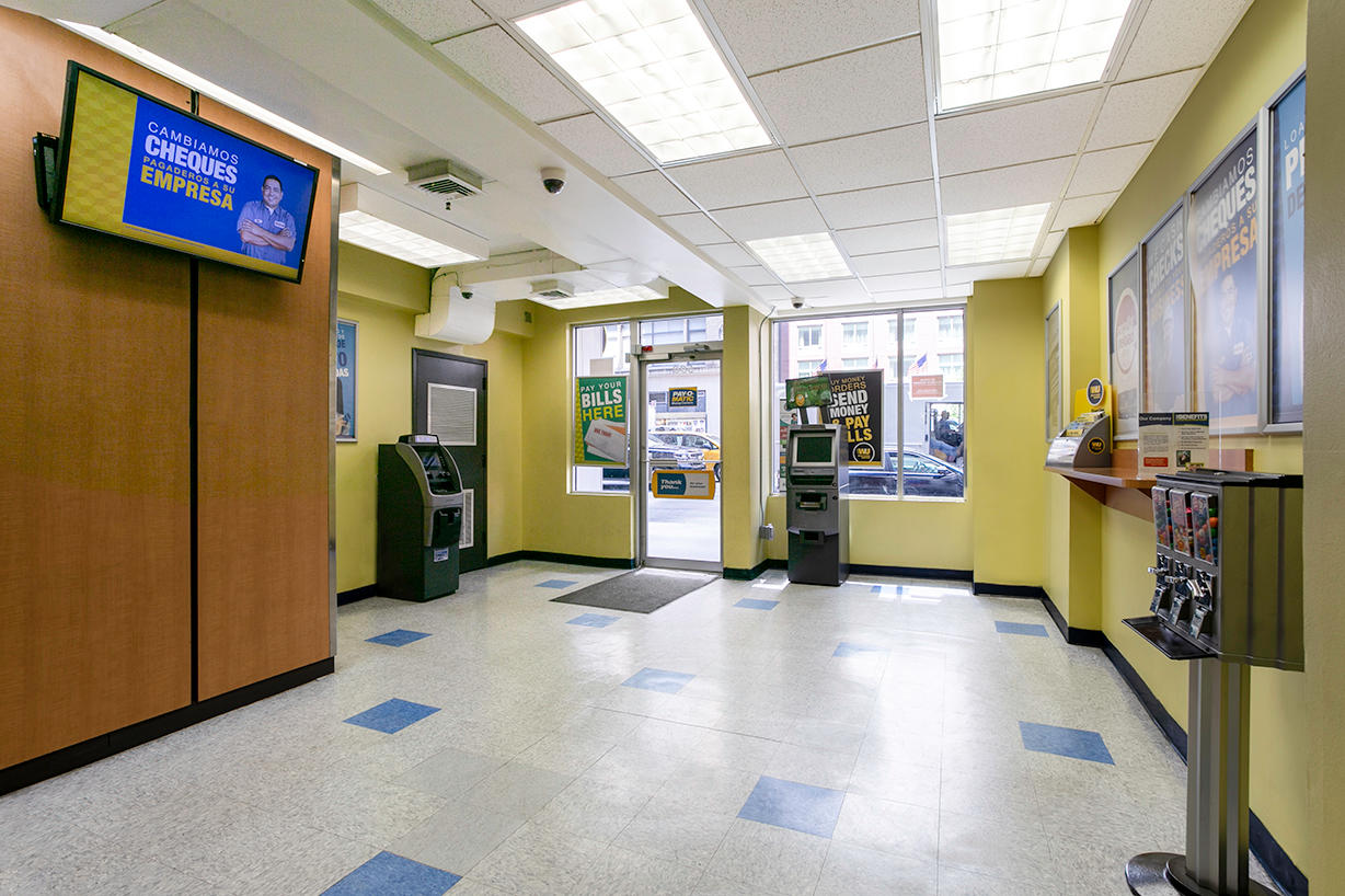 Customer waiting area and entrance inside PAYOMATIC store located at 590 Eight Ave New York, NY 10018