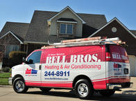 Bell Brothers Heating and Air Conditioning service van in front of a home.