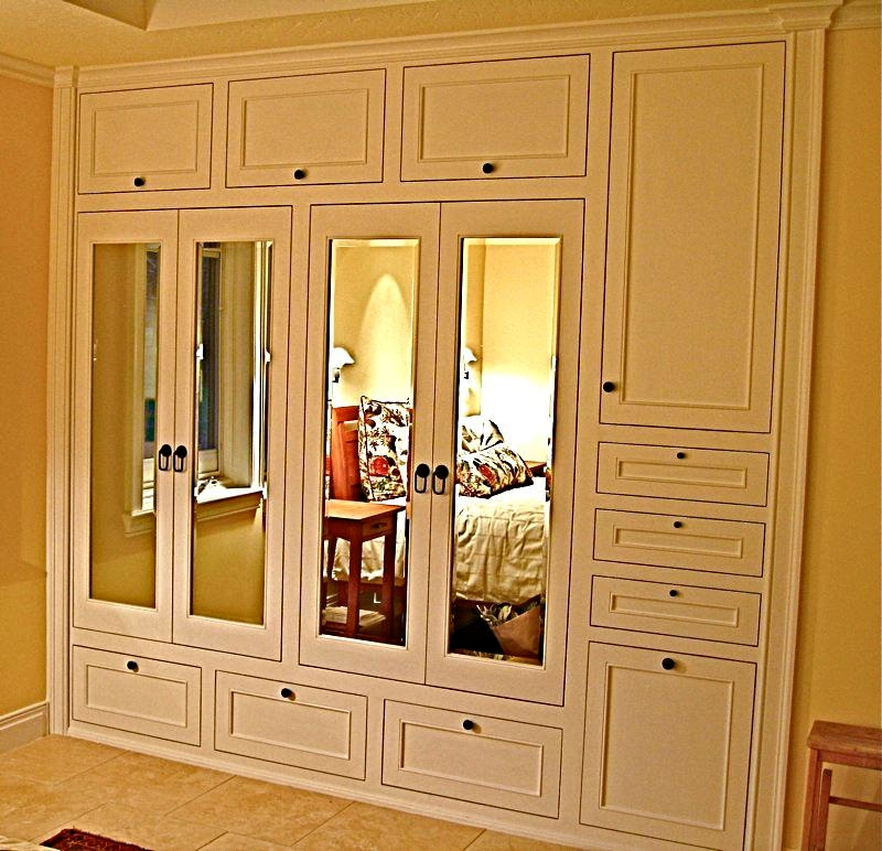 Hers, built in custom closet designed and handcrafted by Philip Snyder of PS Woodworking features columns, flush doors, beveled mirror doors, interior lighting, aromatic Cedar lining throughout, a laundry hamper and a shoe rack.