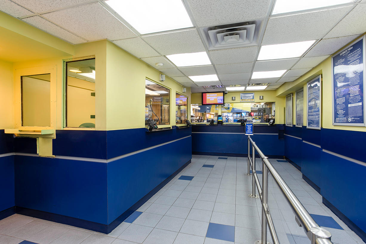 Inside view of customer line area and teller window for PAYOMATIC store located at 94 Eight Ave New York, NY 10001