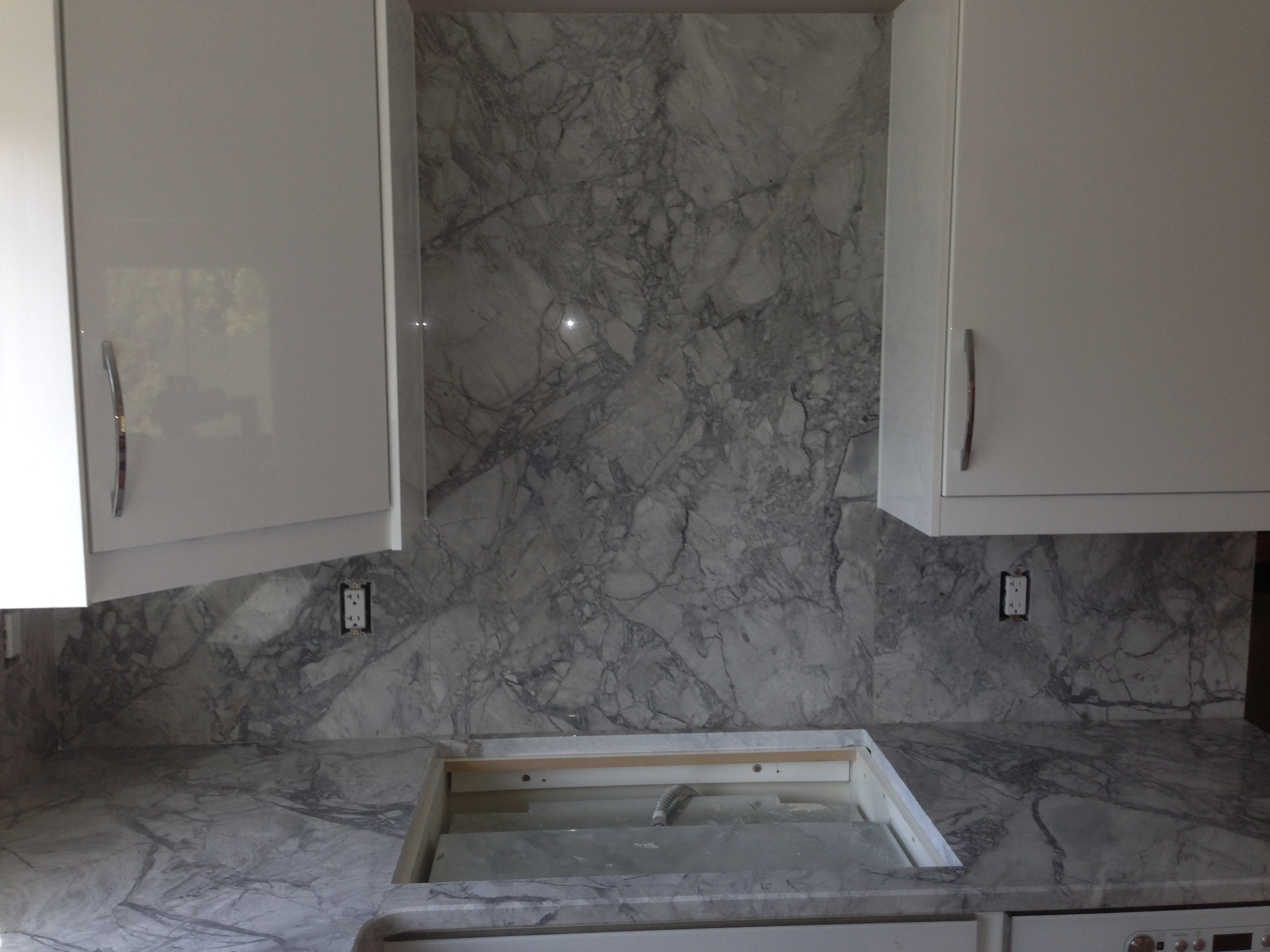 Super White Exotic Kitchen Granite Countertops With Full Granite Backsplash  And Cooktop Cut Out In Troy, MI.