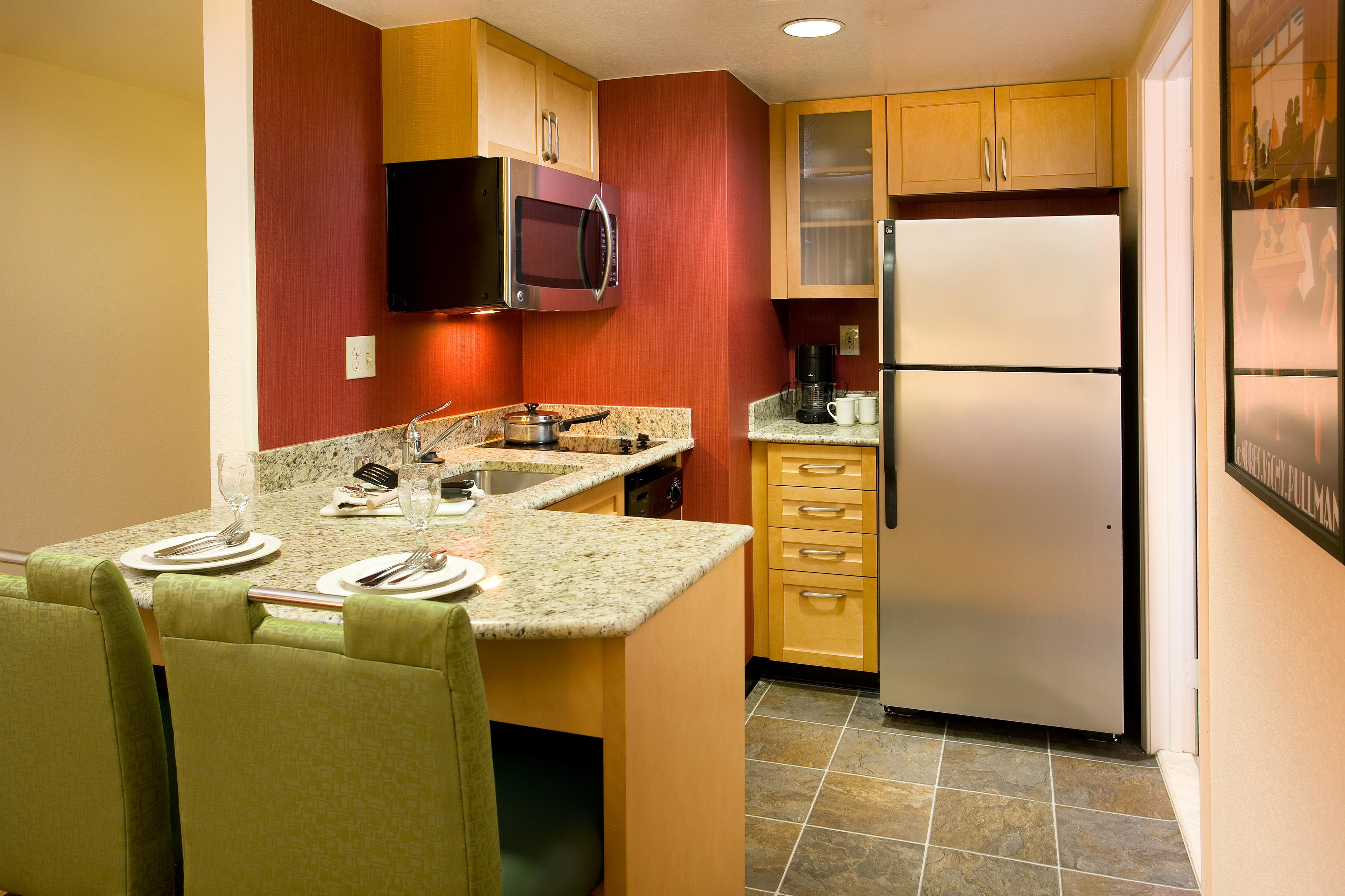 One-Bedroom Suite Kitchen - Kitchens in our one-bedroom suites feature a refrigerator, stove, microwave, toaster, pots, pans, dishes, silverware, glassware and dishwasher so you feel right at home.