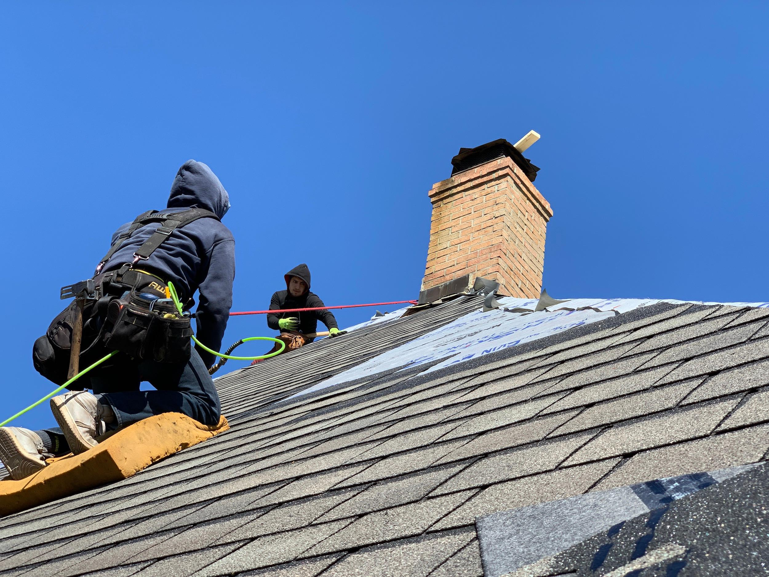 Roofing contractor in Indiana installing a shingle roof on another home.