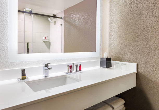 Our spacious guest bathrooms showcase sleek accents and a back-lit vanity mirror.