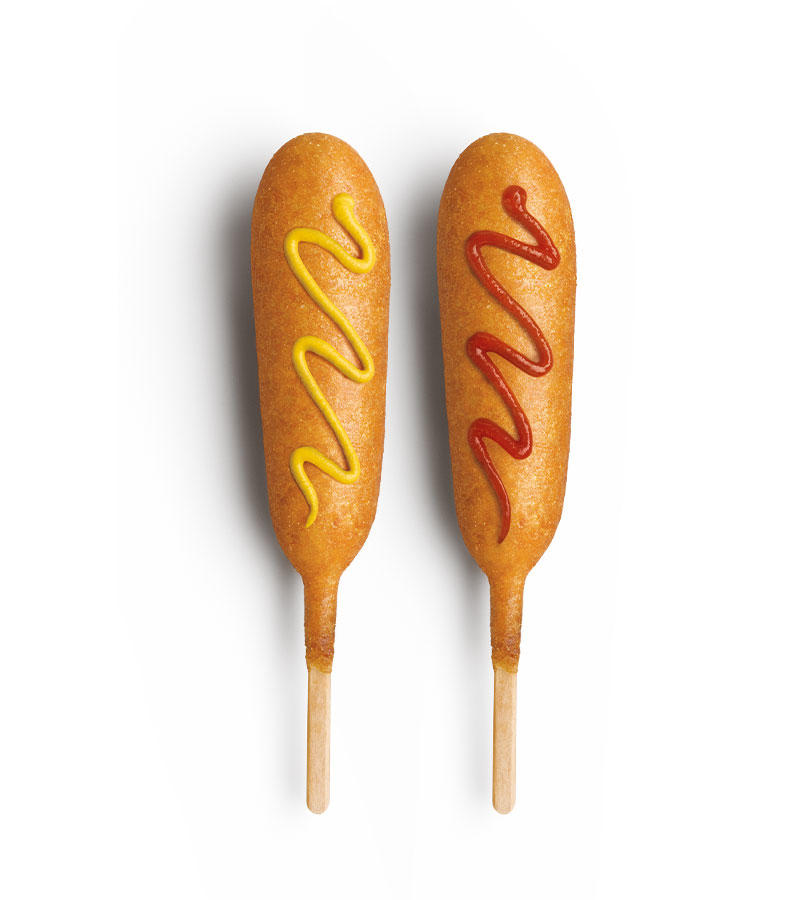A delicious hot dog surrounded in sweet corn batter and fried to a crispy golden brown. Try it with some mustard or ketchup if you want. It's like hot dog utopia on a stick.